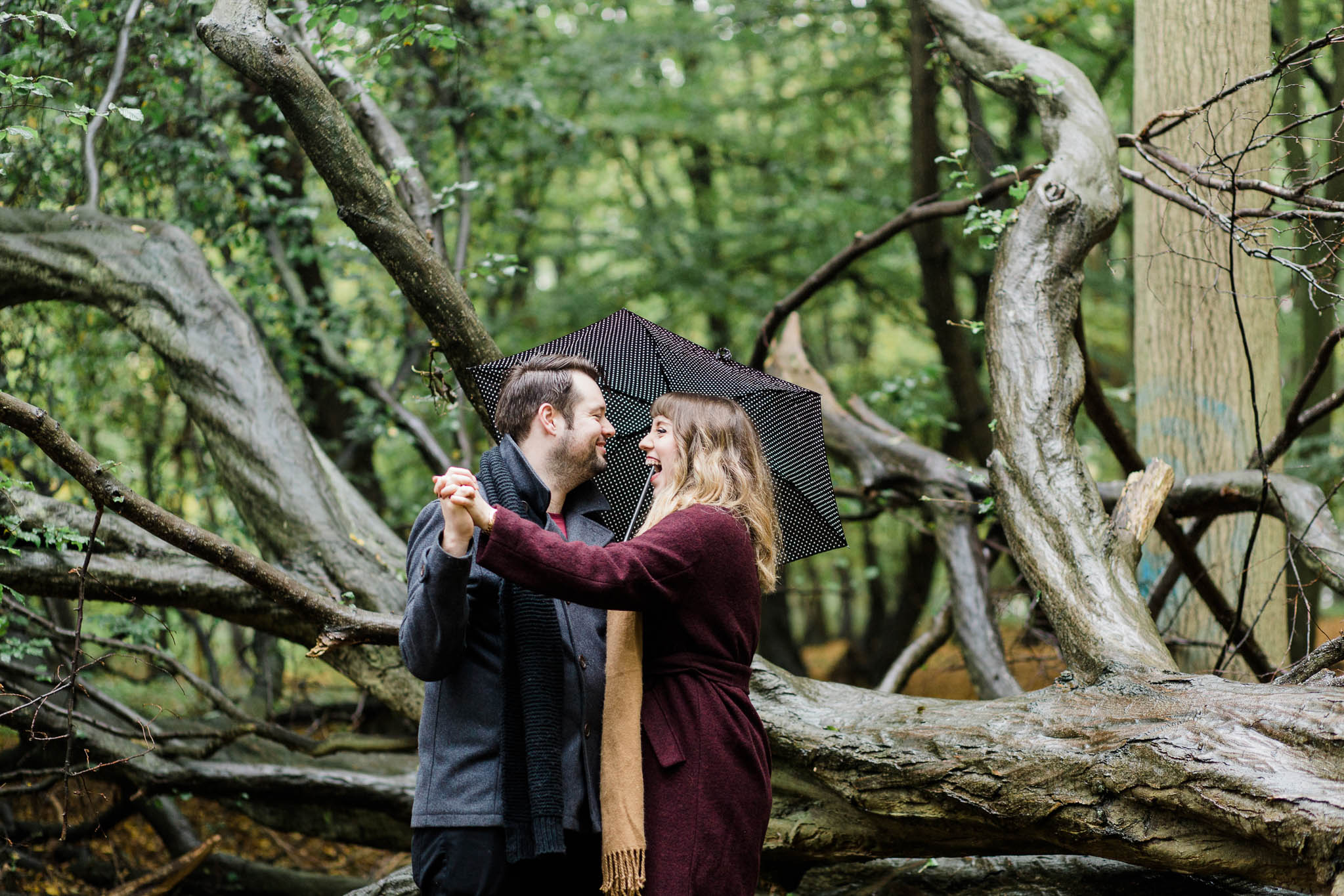 couple in forest for pre-wedding photo shoot in rain