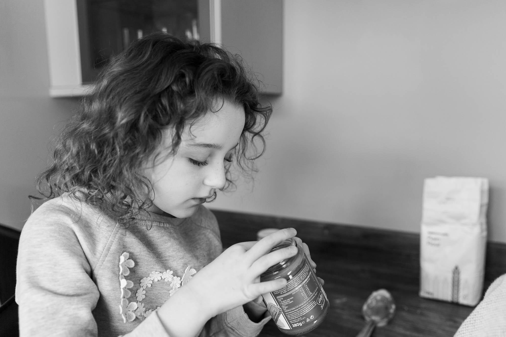 little girl dipping finger into jar