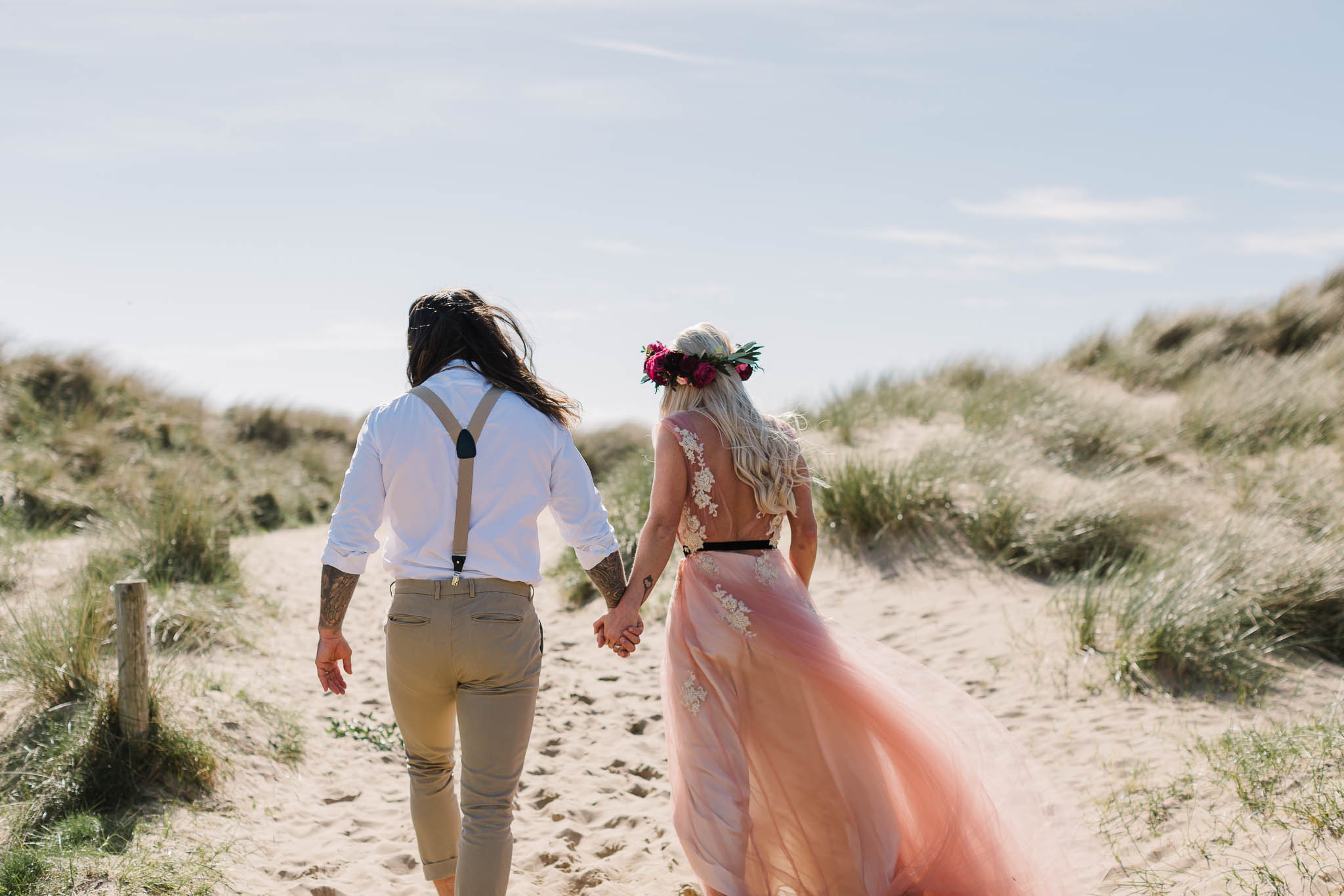 bride and groom walking through sand dunes at beach