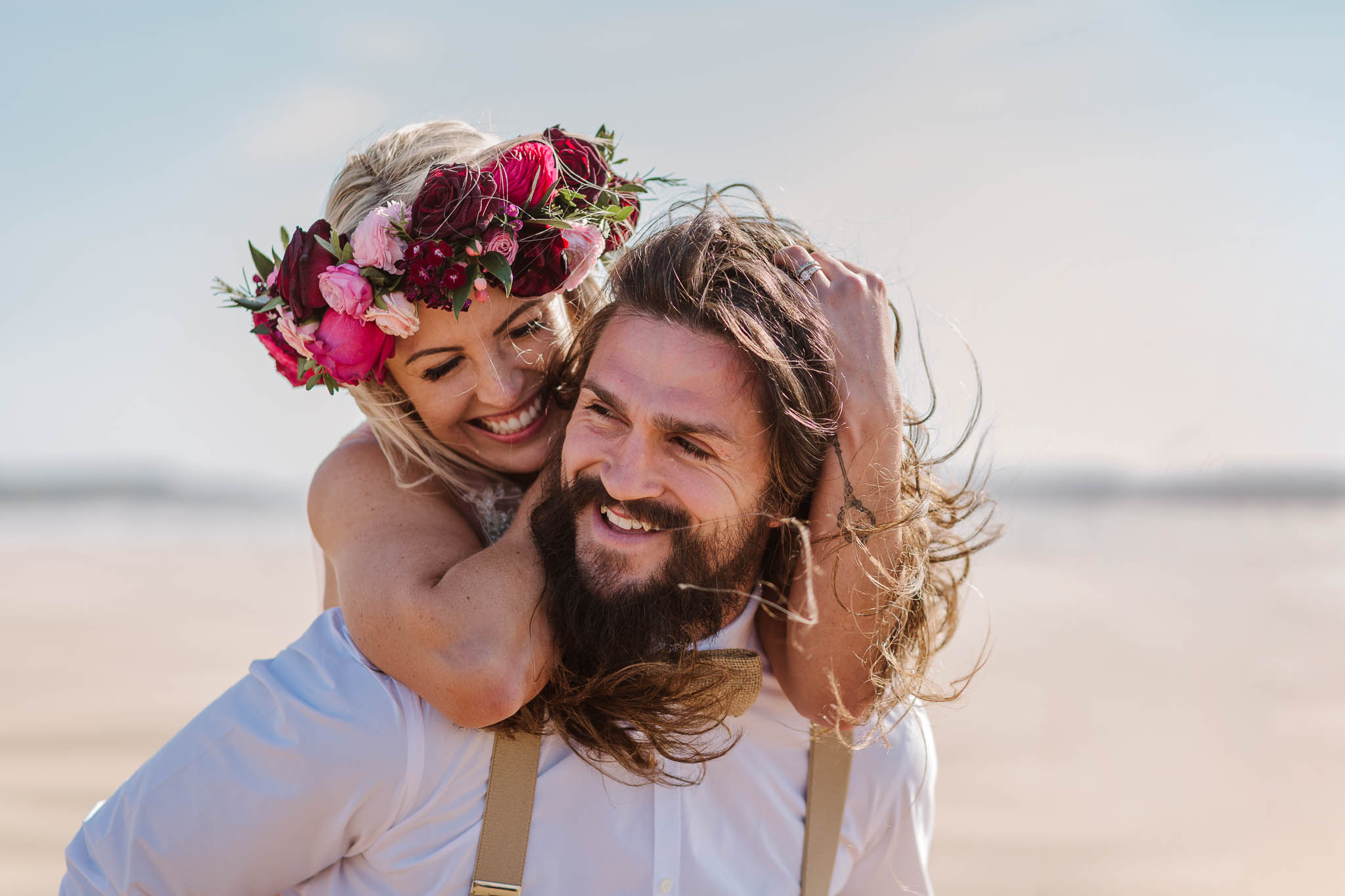 bride and groom on windy beach
