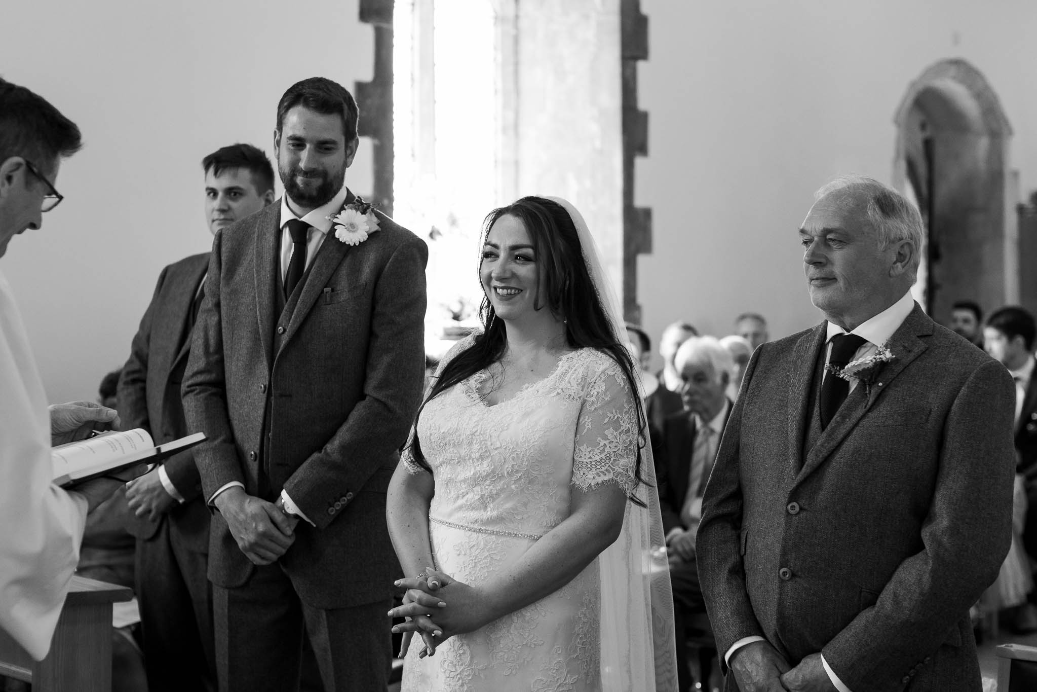 bride and groom smiling during church service