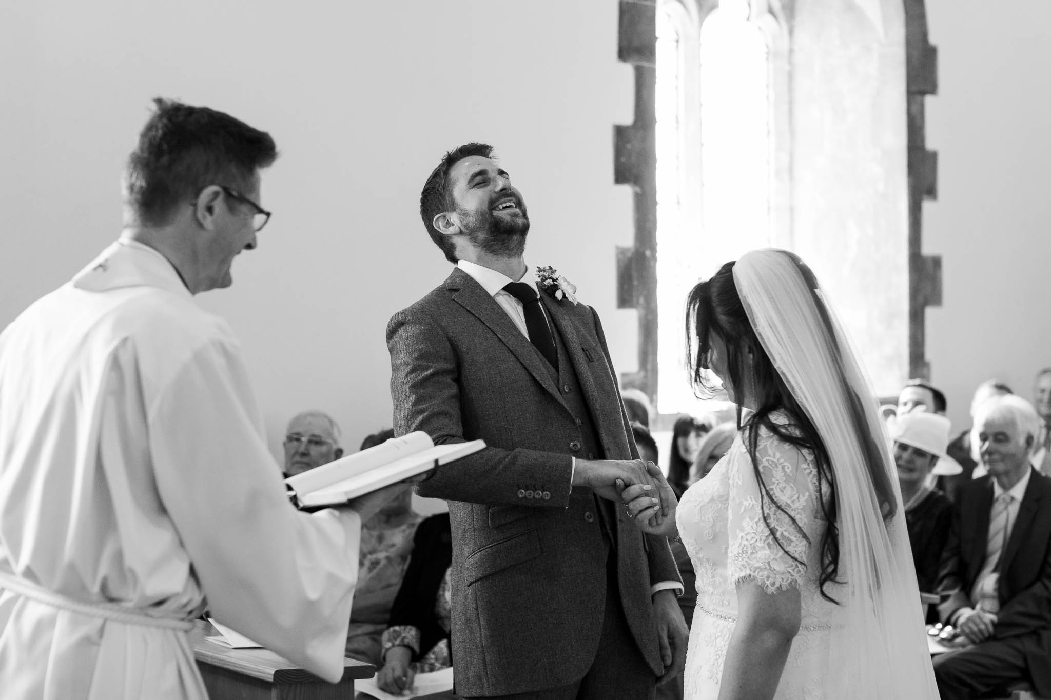 groom laughing during vows