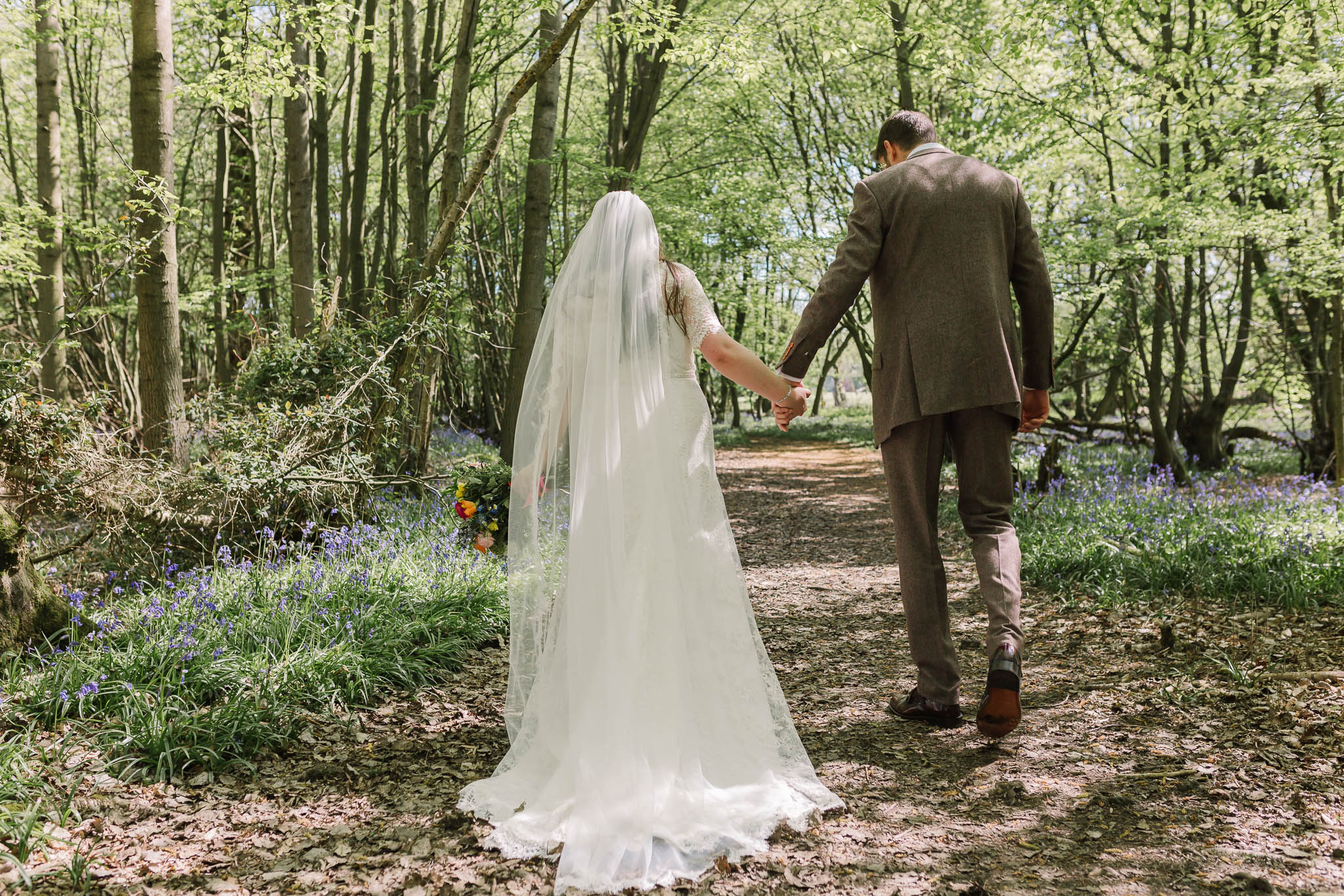 bride and groom walking through bluebell woods
