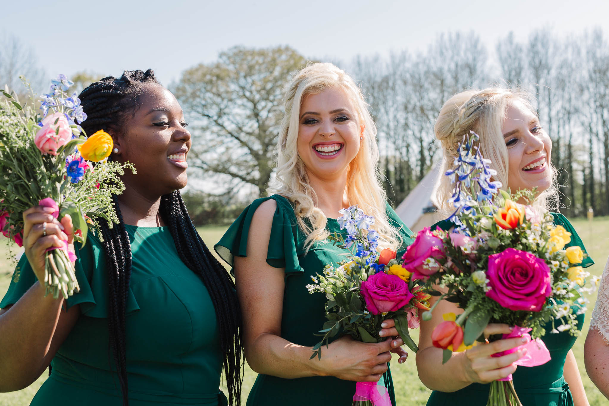 bridesmaids laughing with colourful bouquets