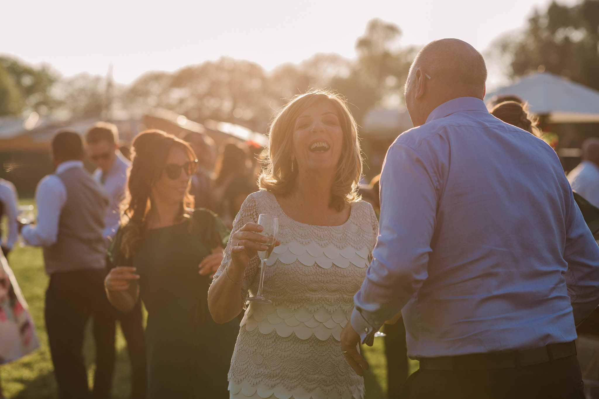 wedding guests dancing outside at sunset