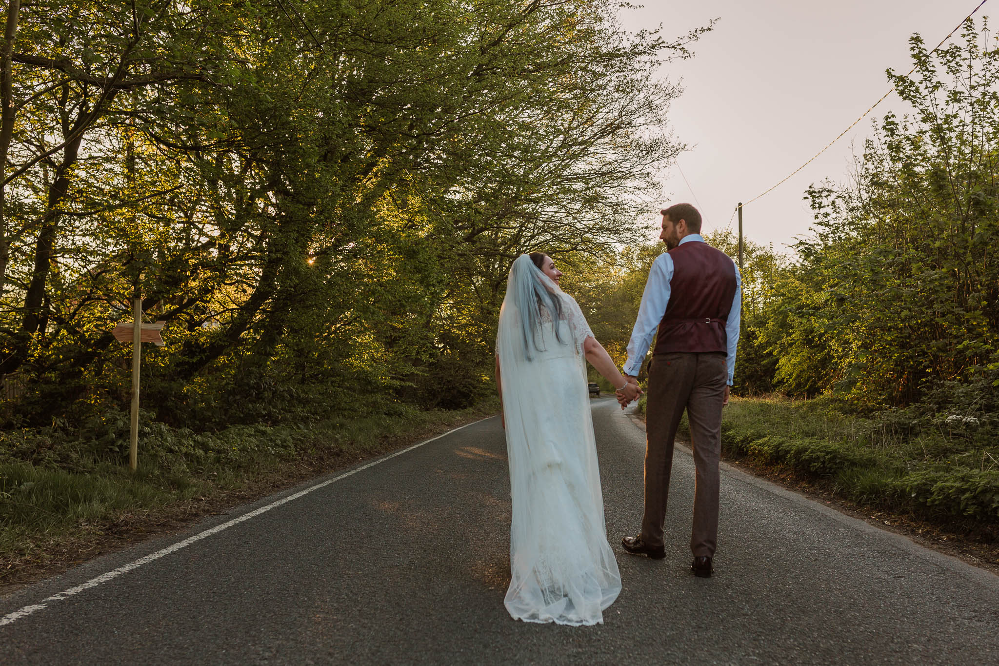 bride and groom walking down road at sunset