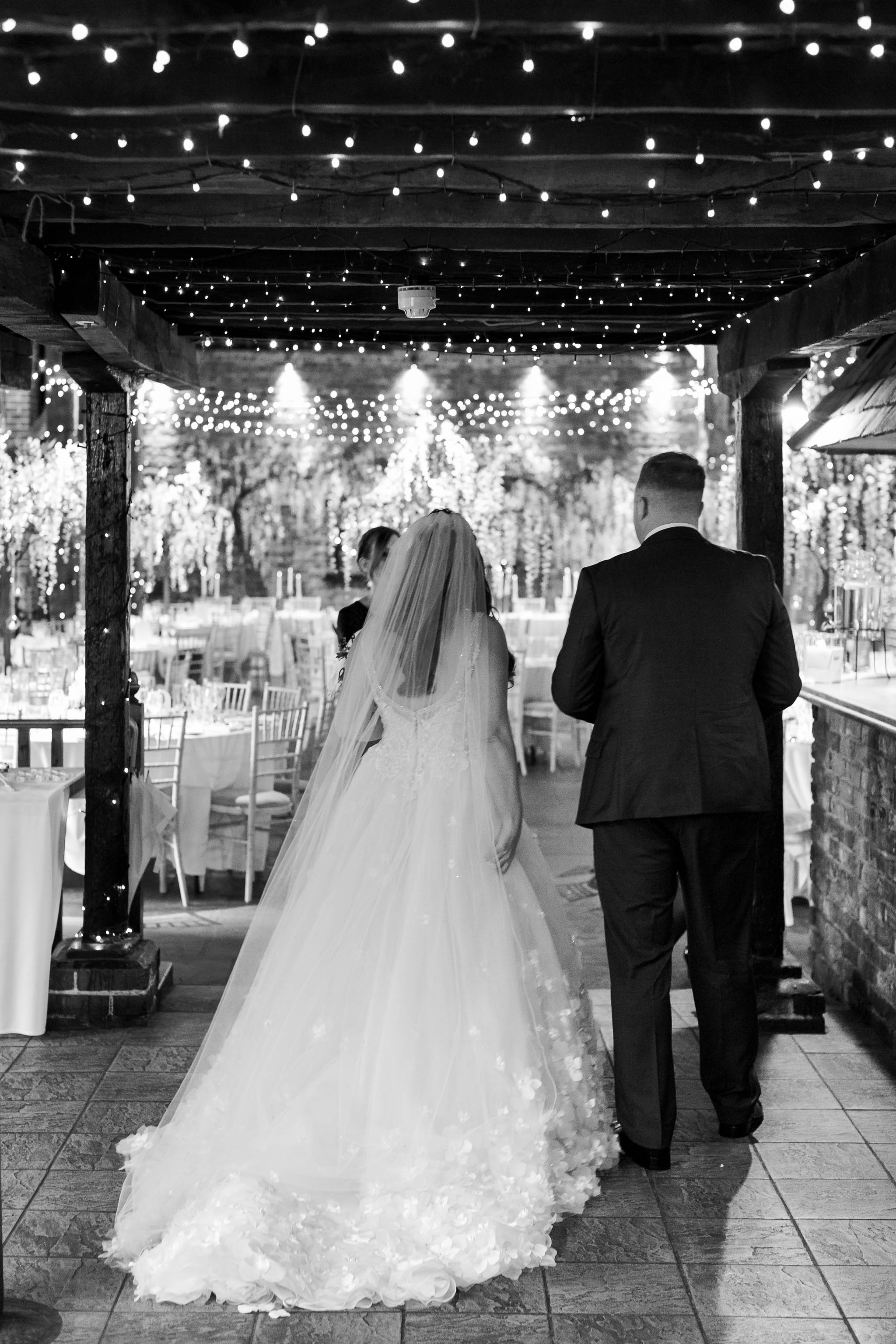 bride and groom walking into barn with twinkle lights