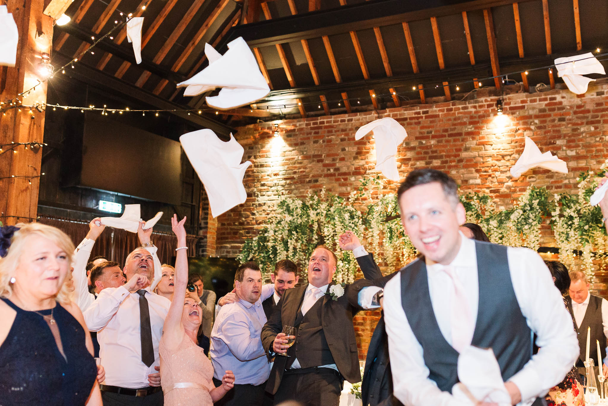 wedding guests throwing napkins in air