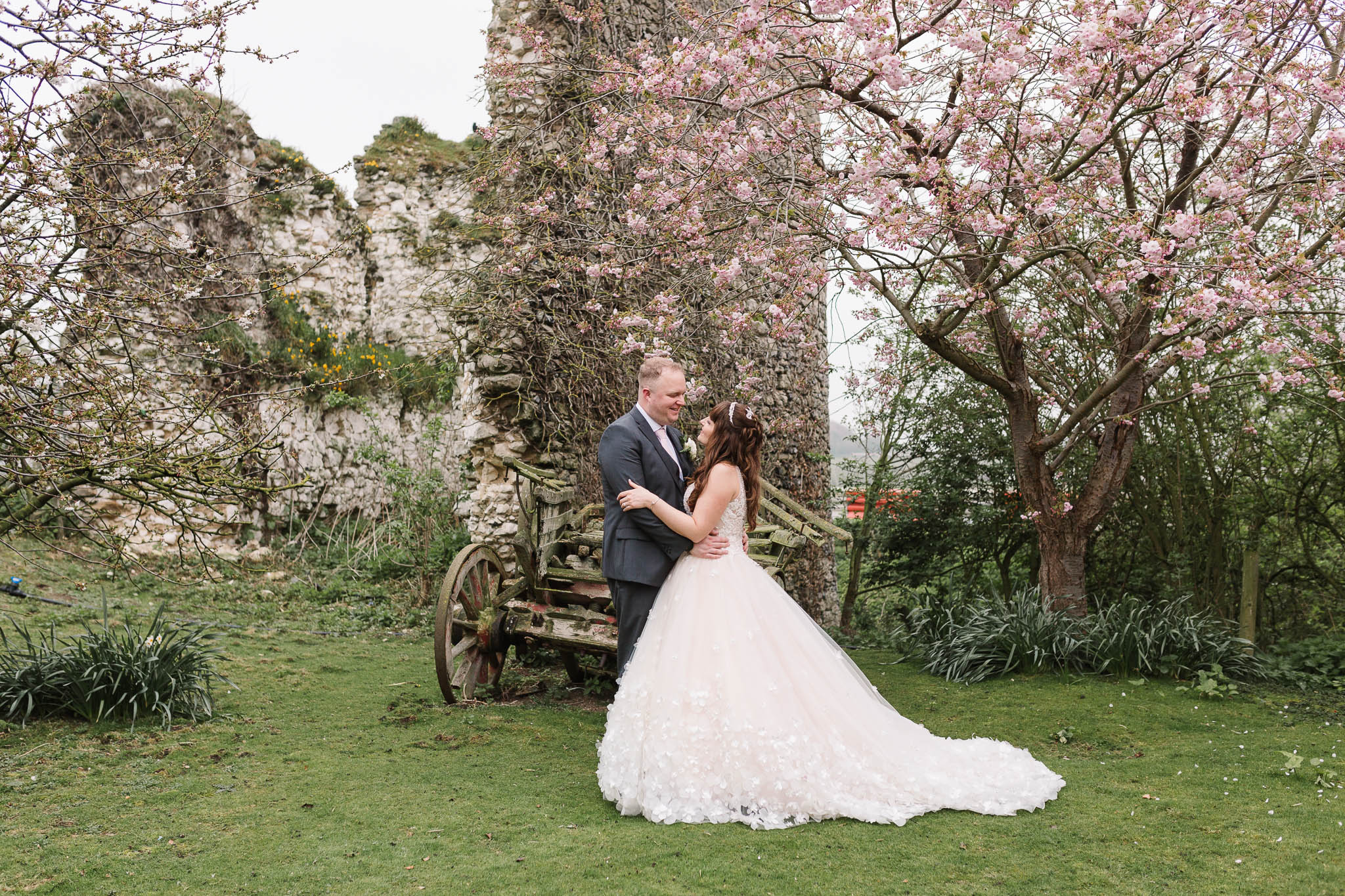 bride and groom with pink blossom trees
