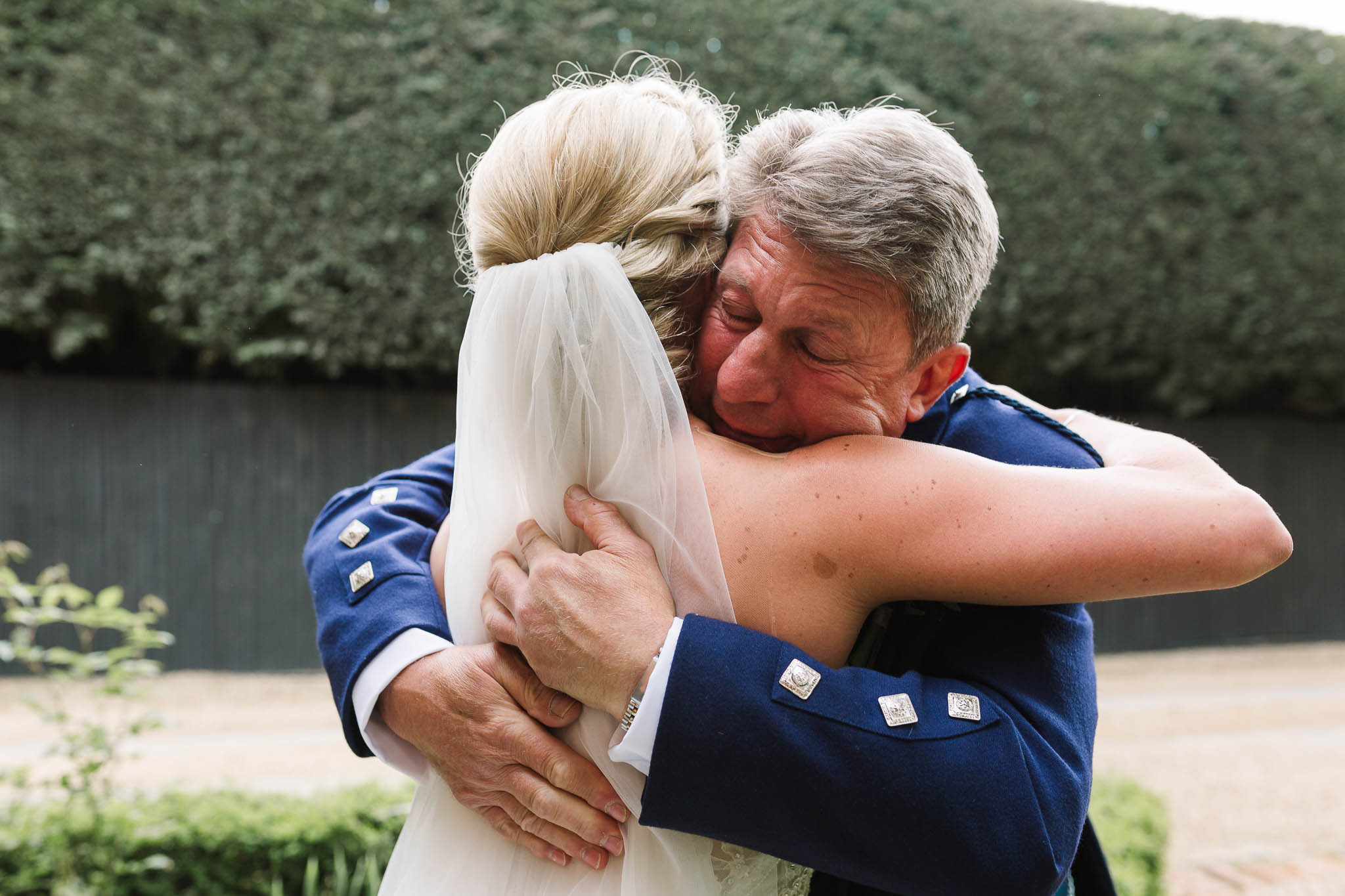father of bride hugging daughter