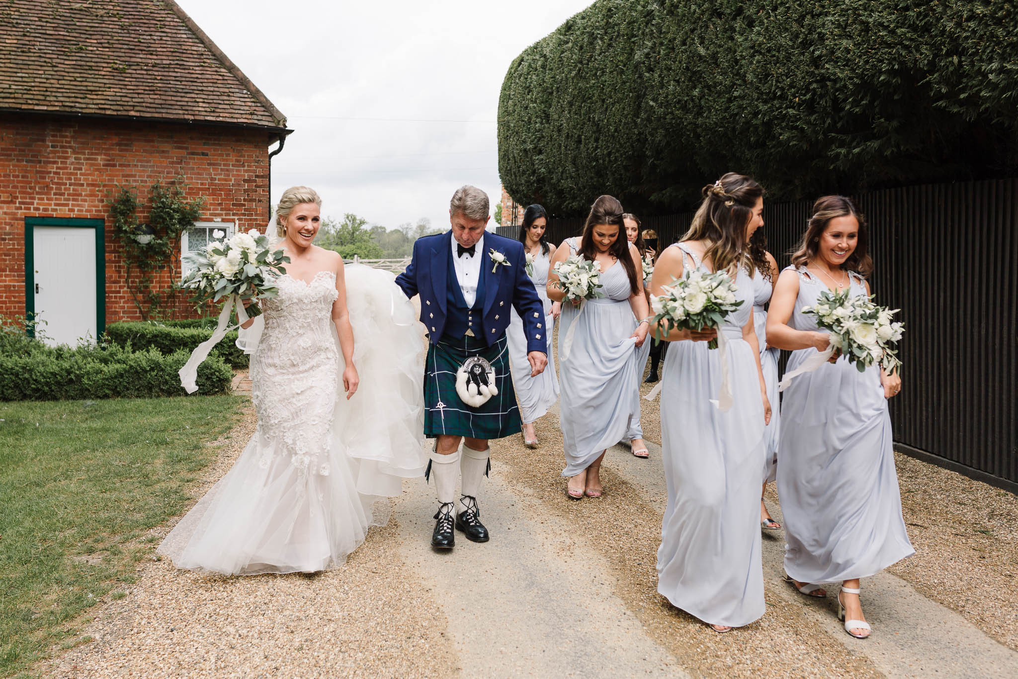 father of the bride and bridesmaids walking towards aisle gaynes park