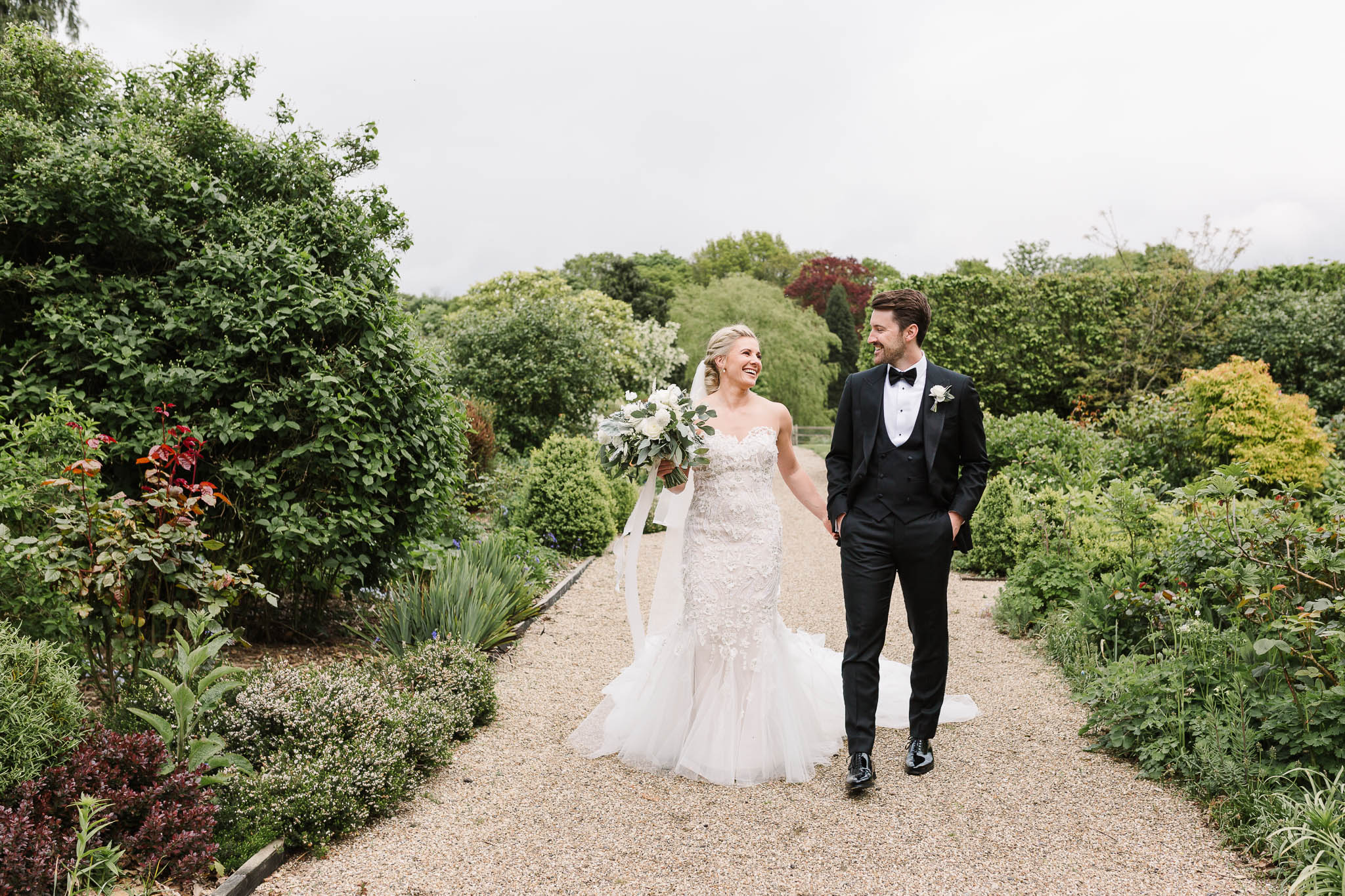 bride and groom walking through gardens at gaynes park