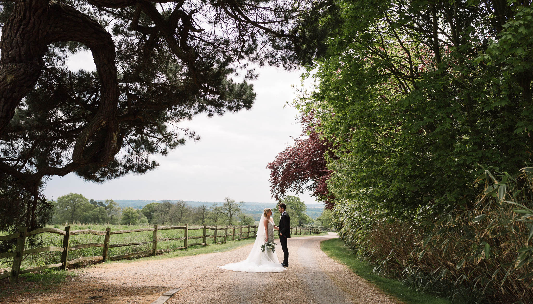 bride and groom under trees at gaynes park