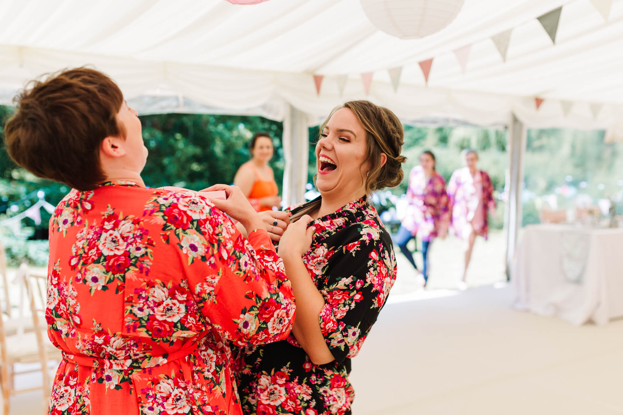 bridesmaids laughing in floral robes