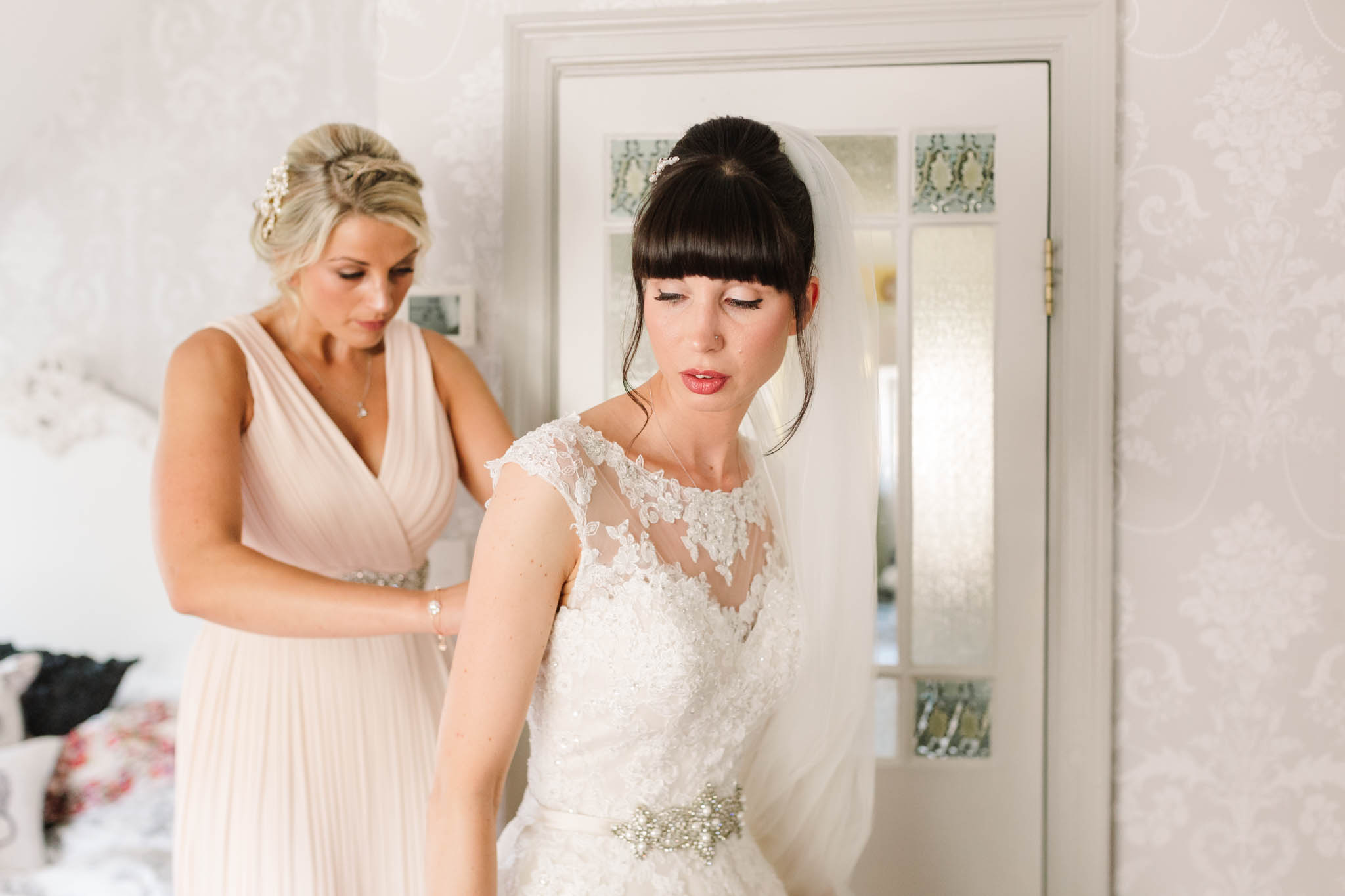 bridesmaid doing up back of brides dress