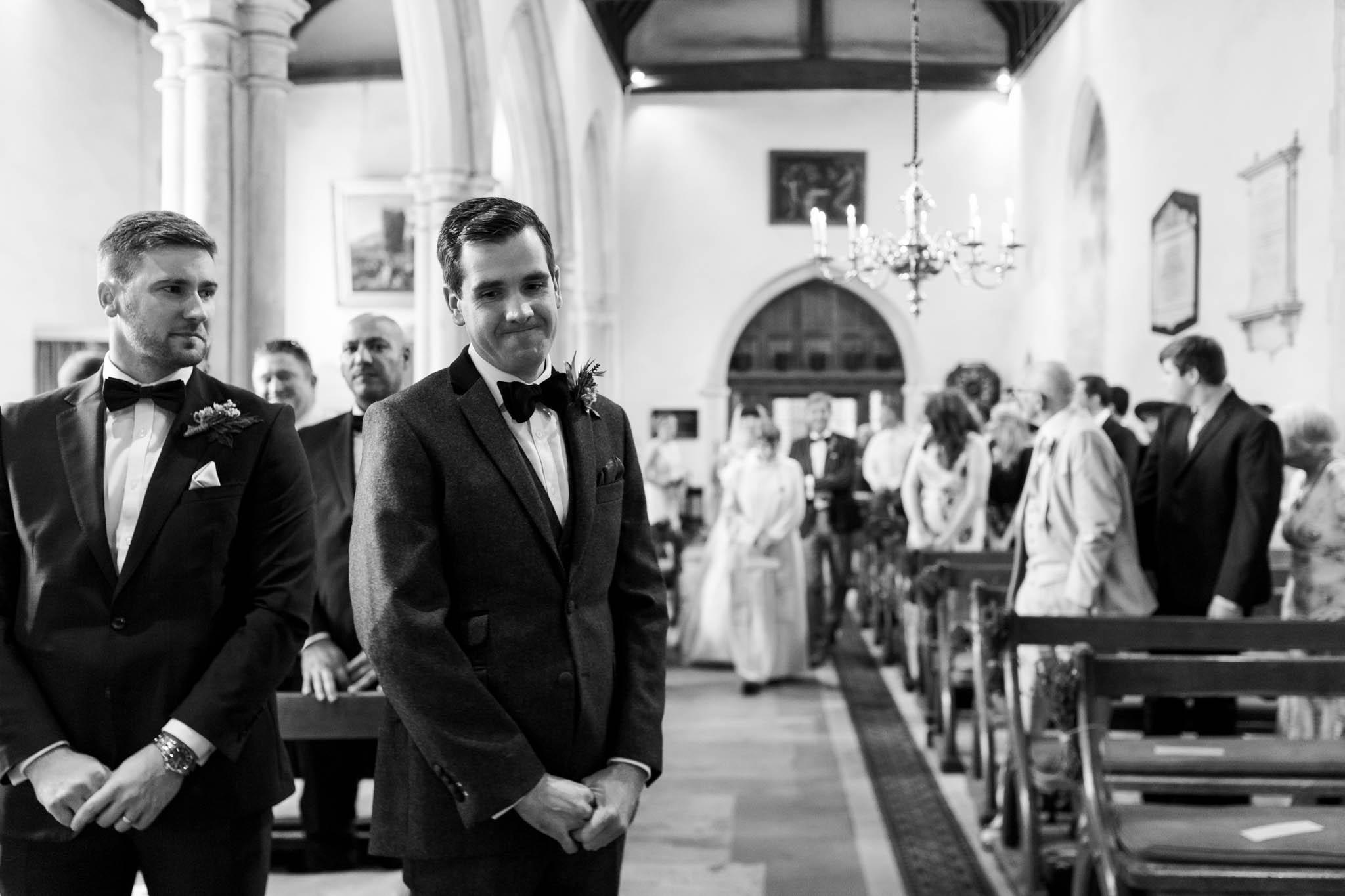 groom waiting as bride walks down aisle