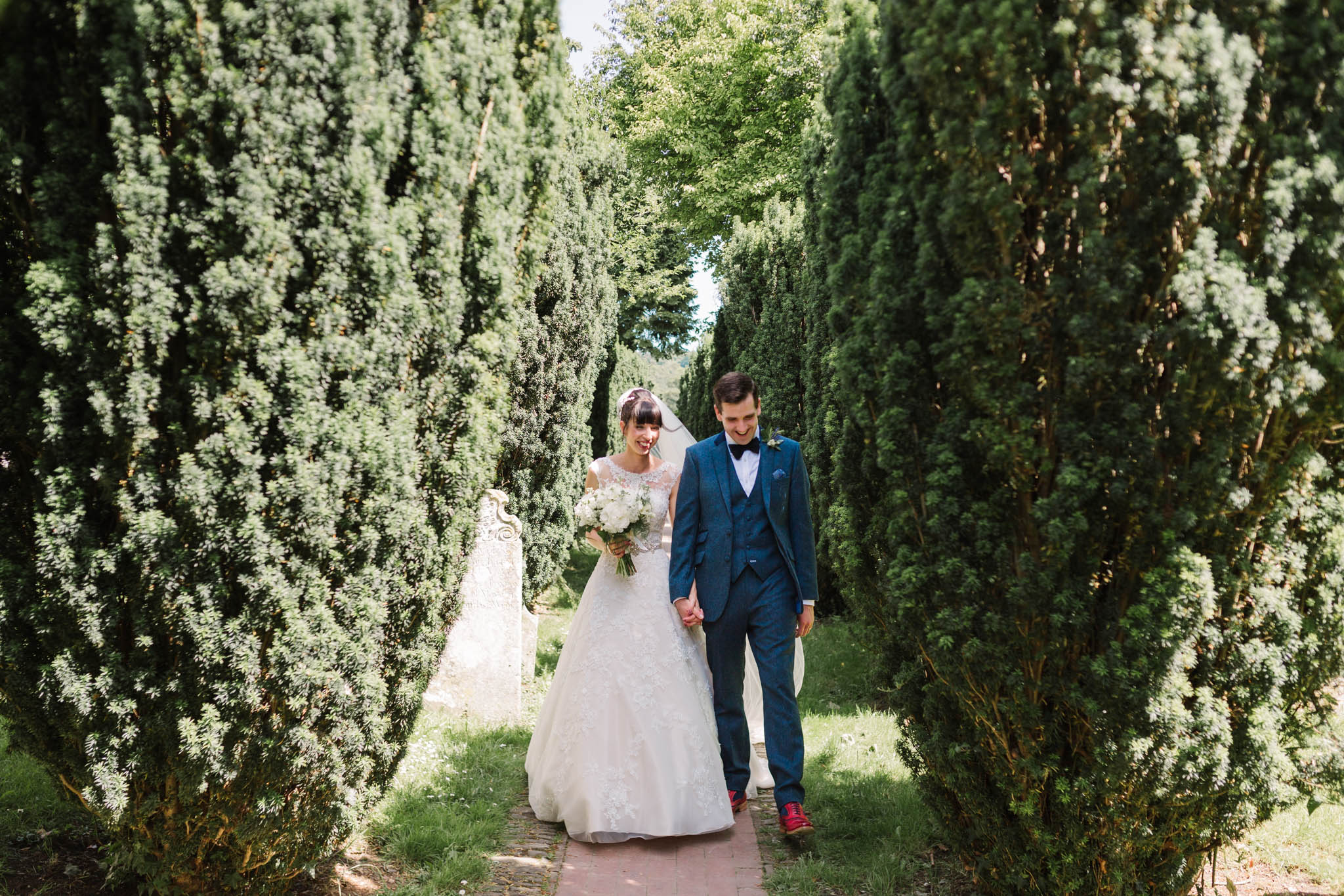 bride and groom walking down tree lined path
