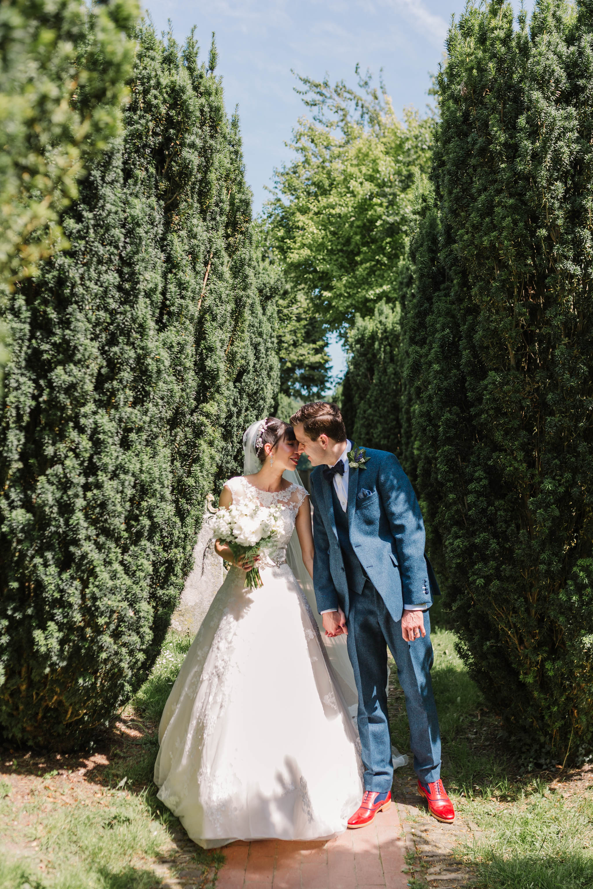 bride and groom kissing down tree lined path