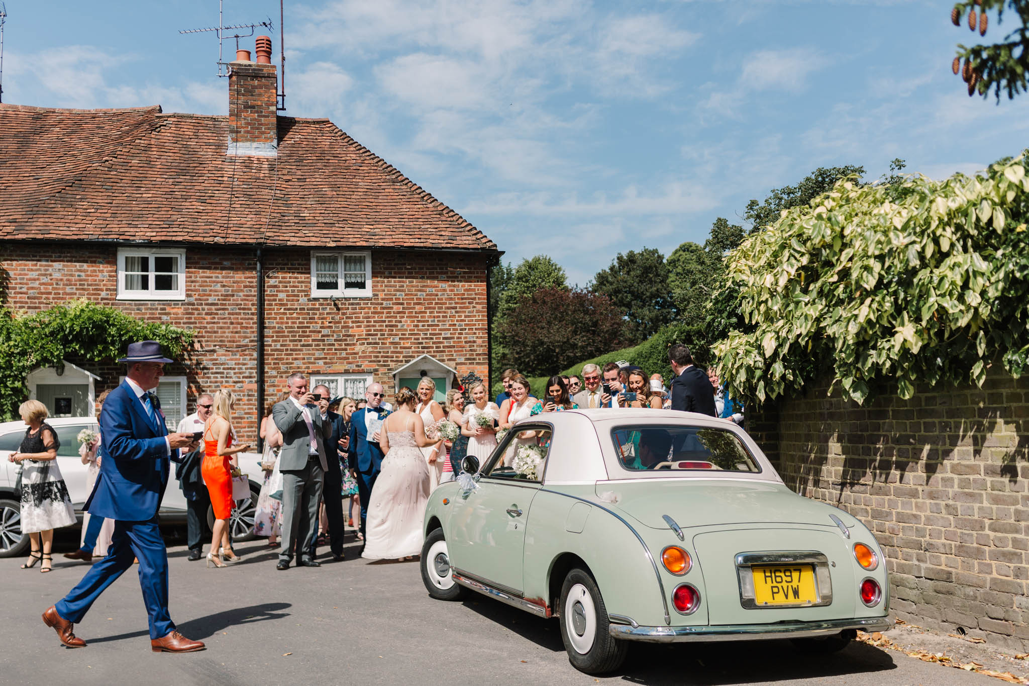 bride and groom in vintage car surrounded by guests