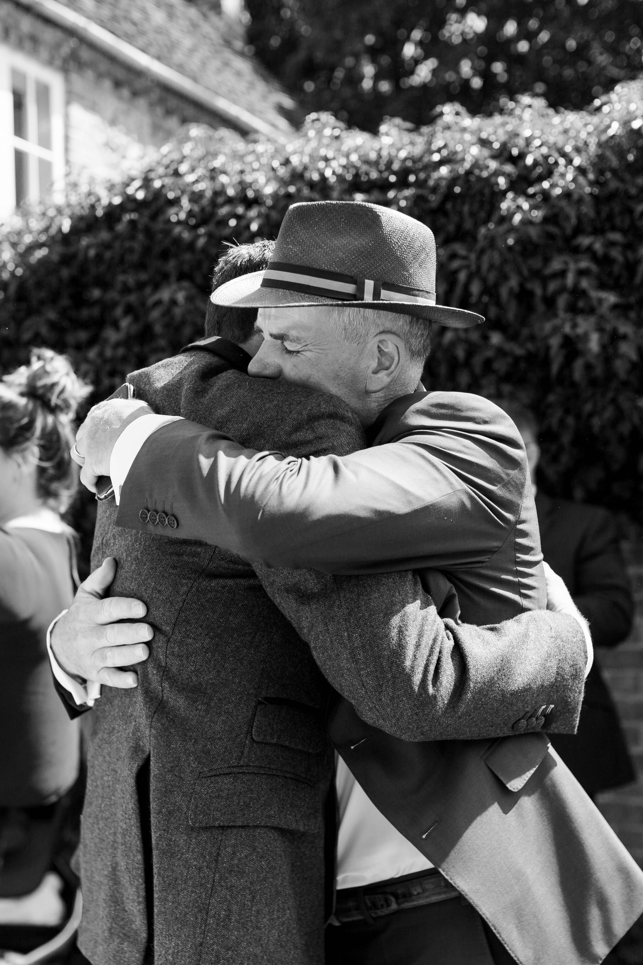 dad hugging his son after wedding