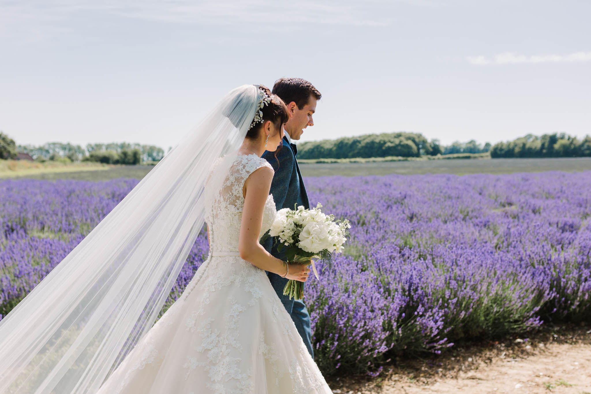 bride and groom walking through lavender field