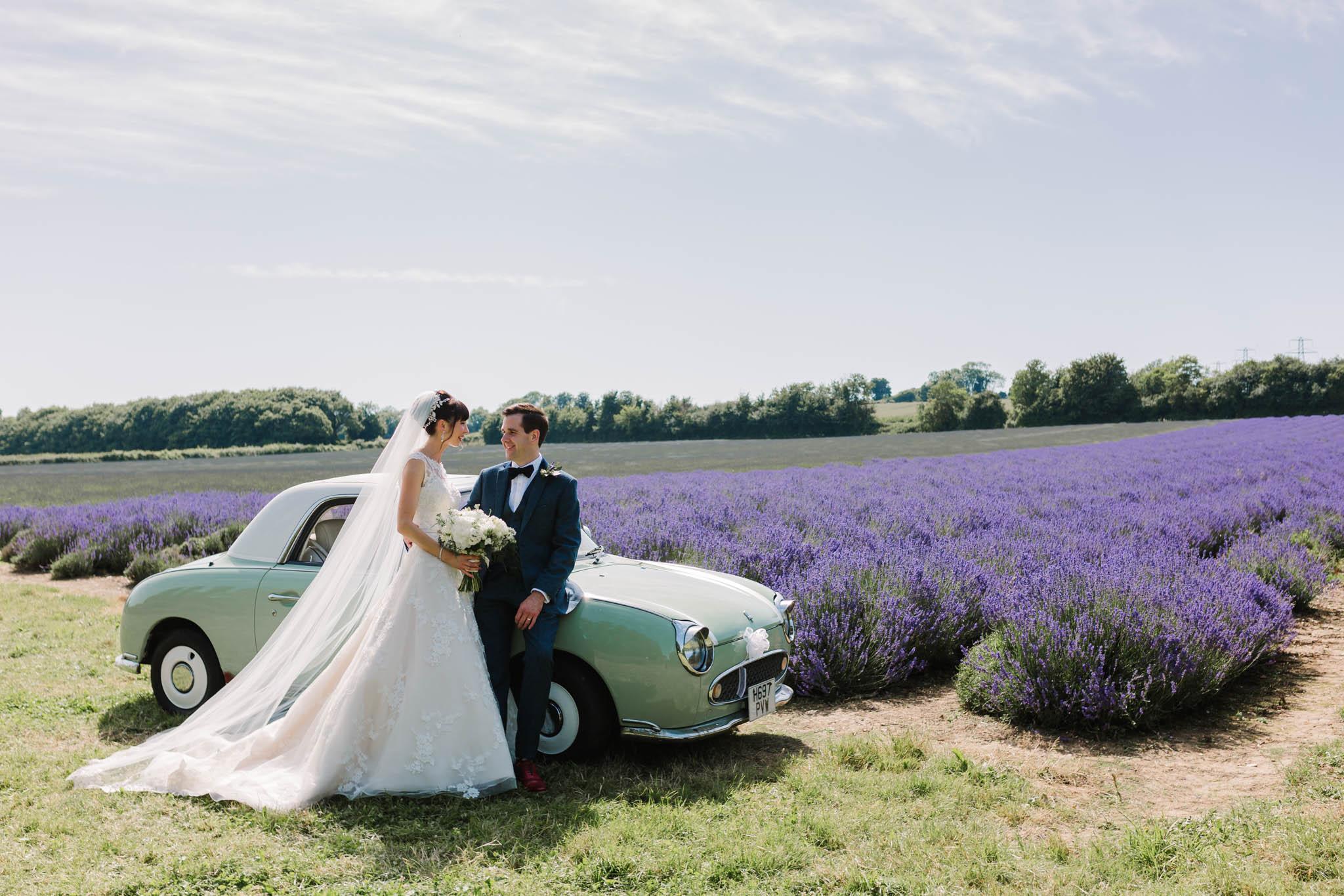 bride and groom with vintage car in lavender field