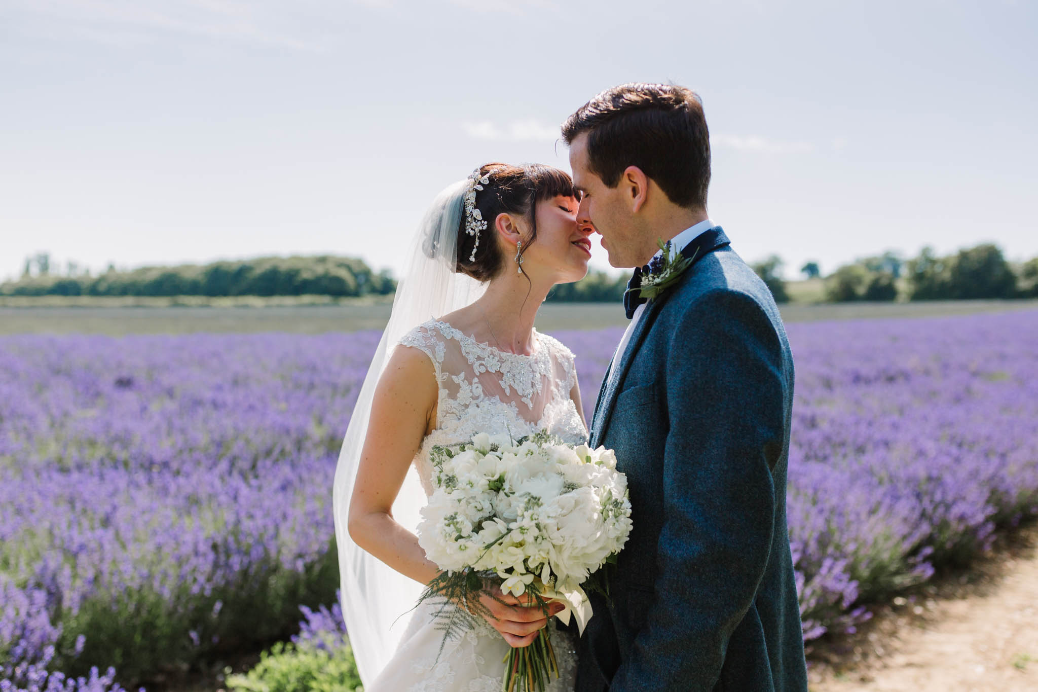 bride and groom kissing in lavender field