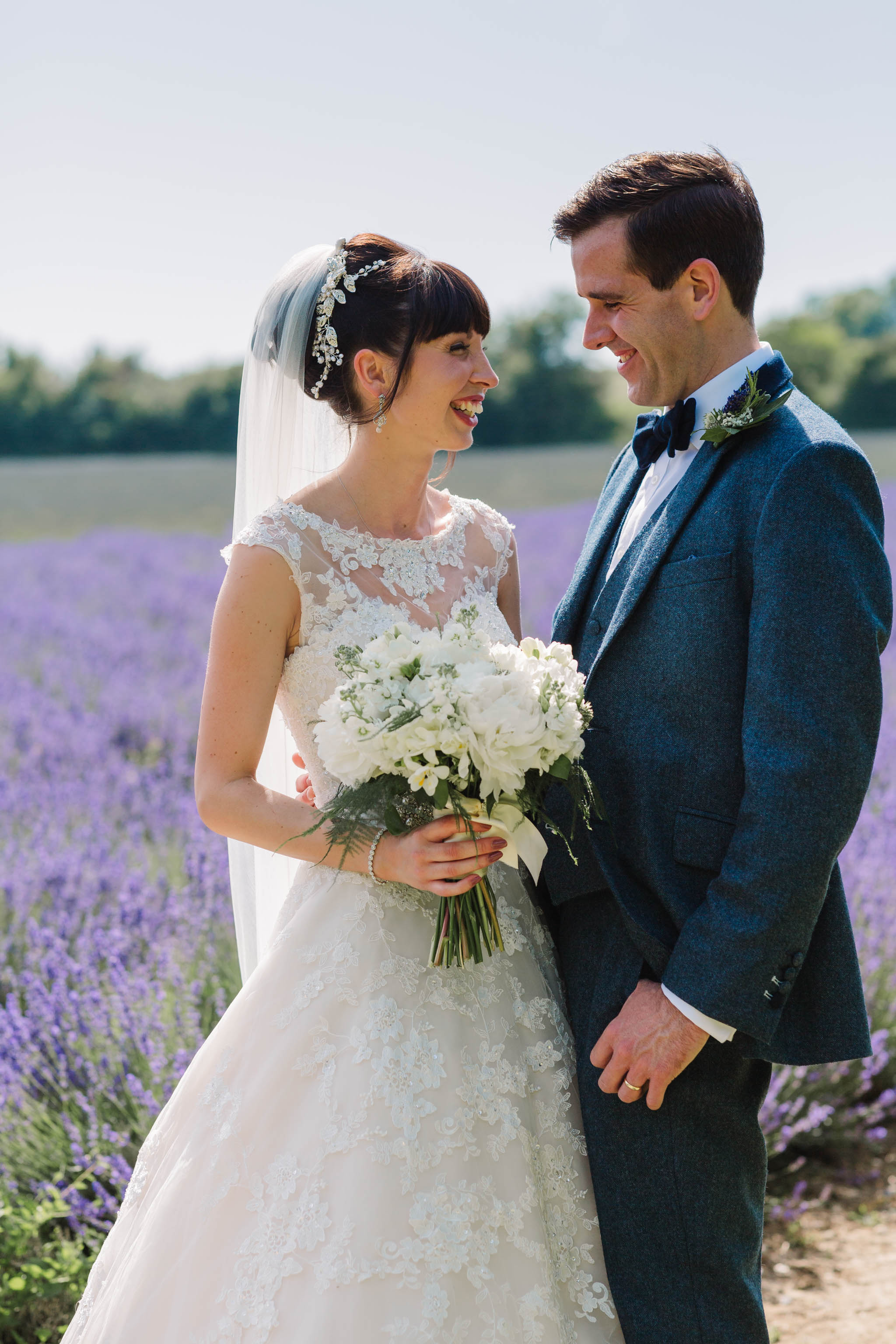 bride and groom laughing in lavender field