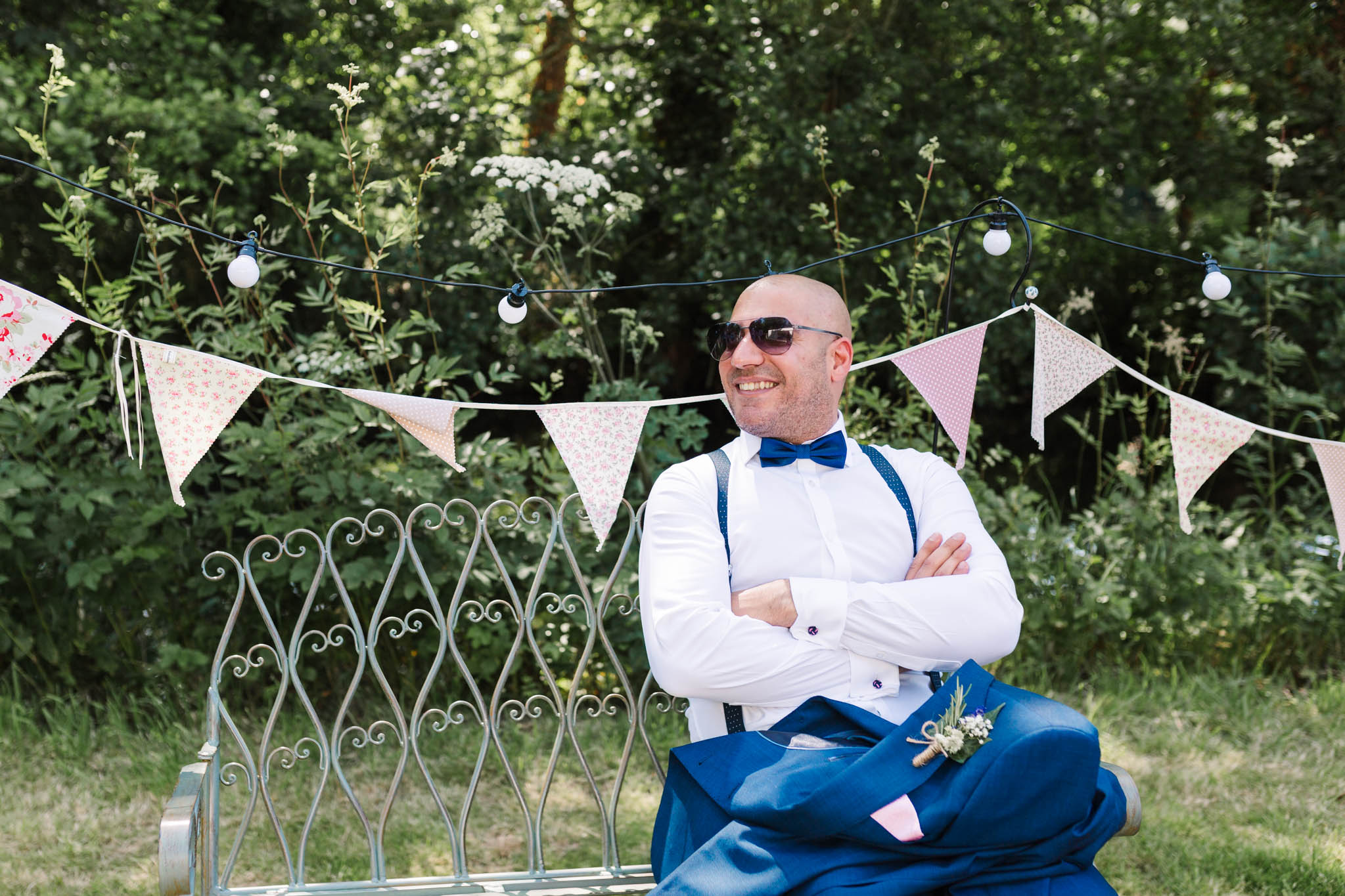 groomsman sitting on bench with vintage bunting