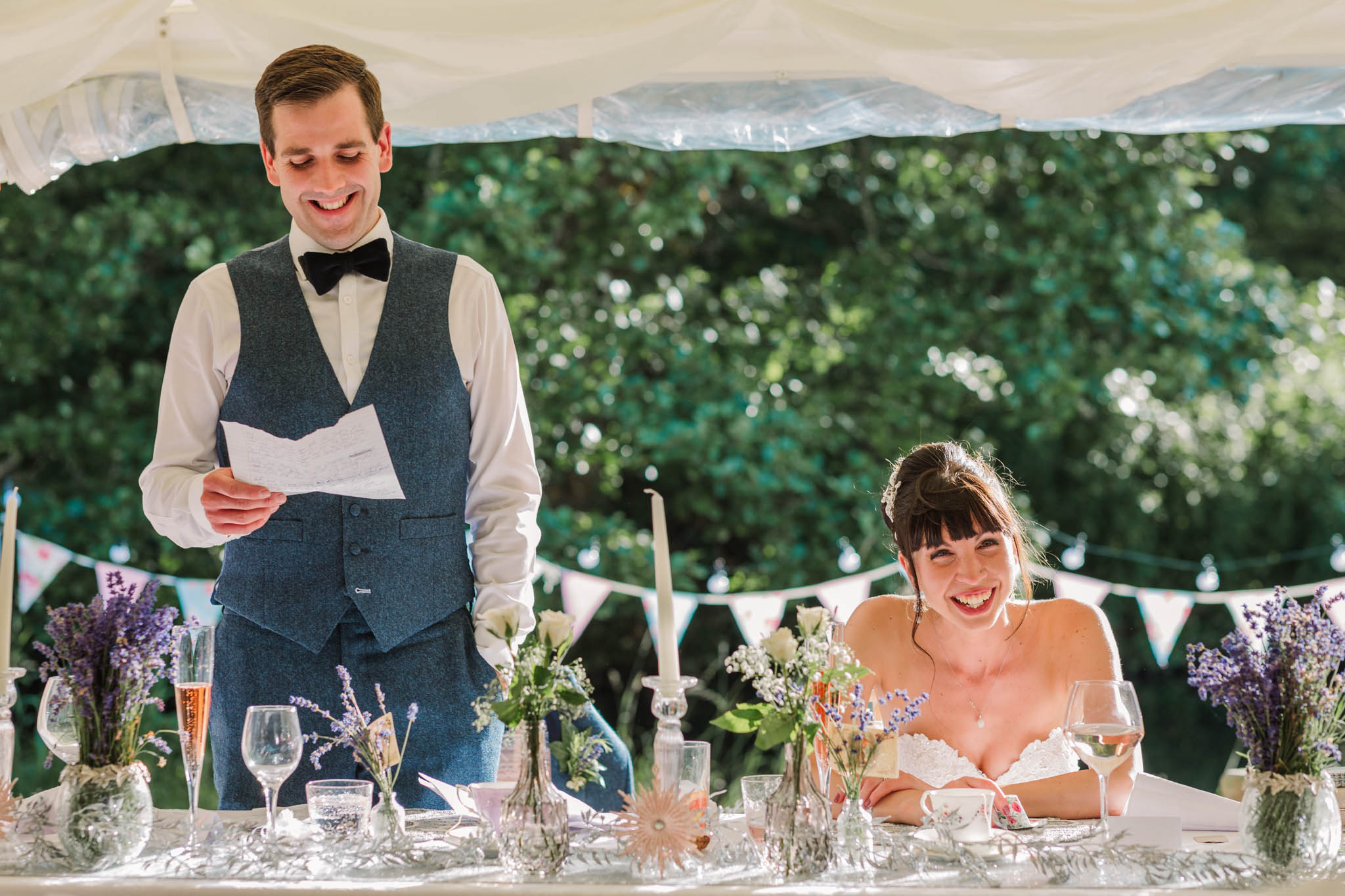 groom giving speech and wife laughing