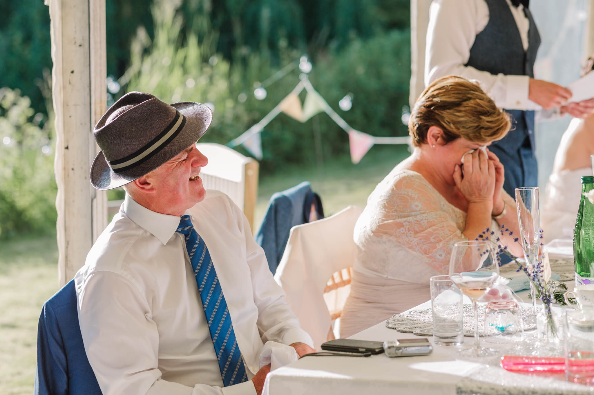 parents laughing and crying at wedding speeches