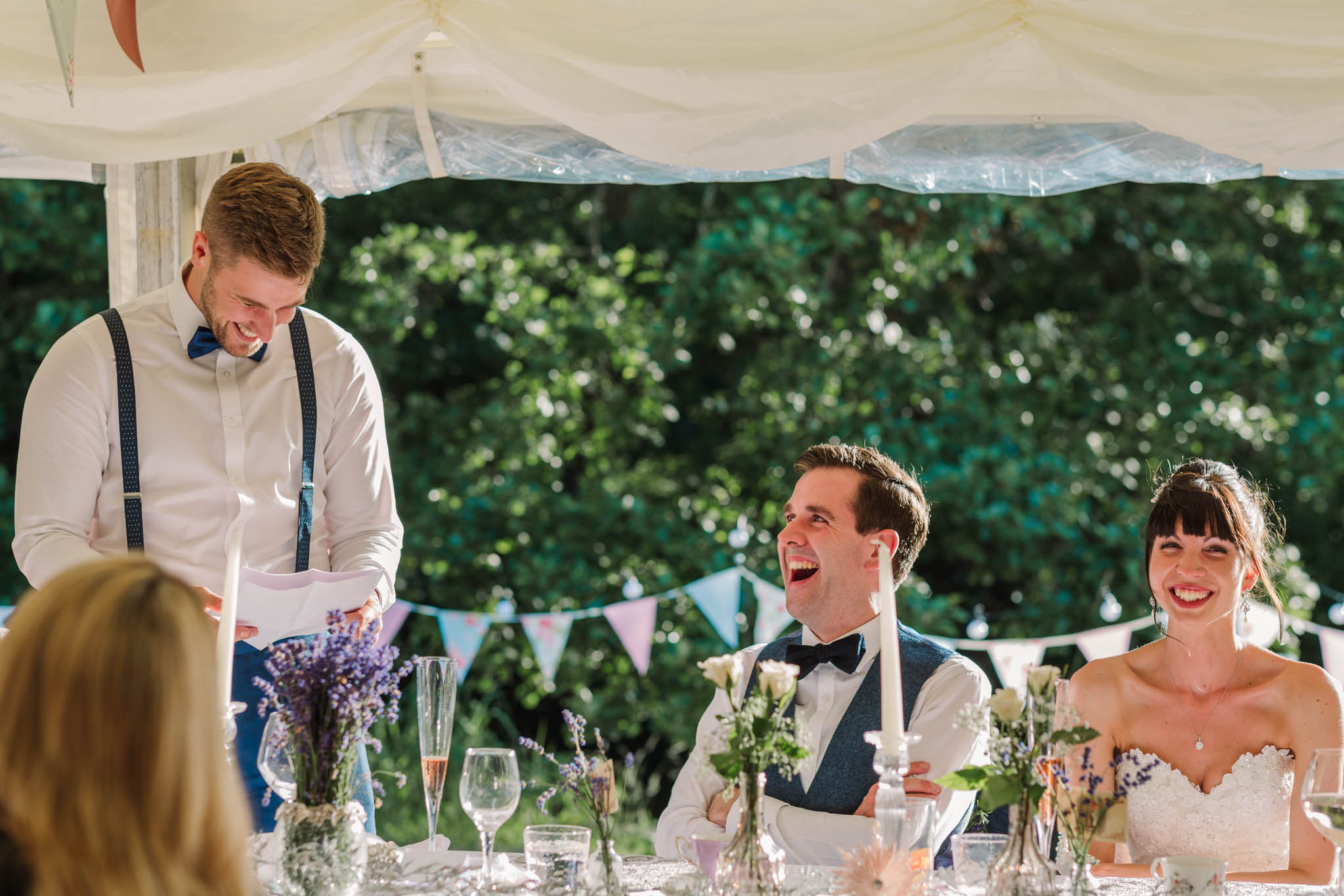best man and bride and groom laughing at speech