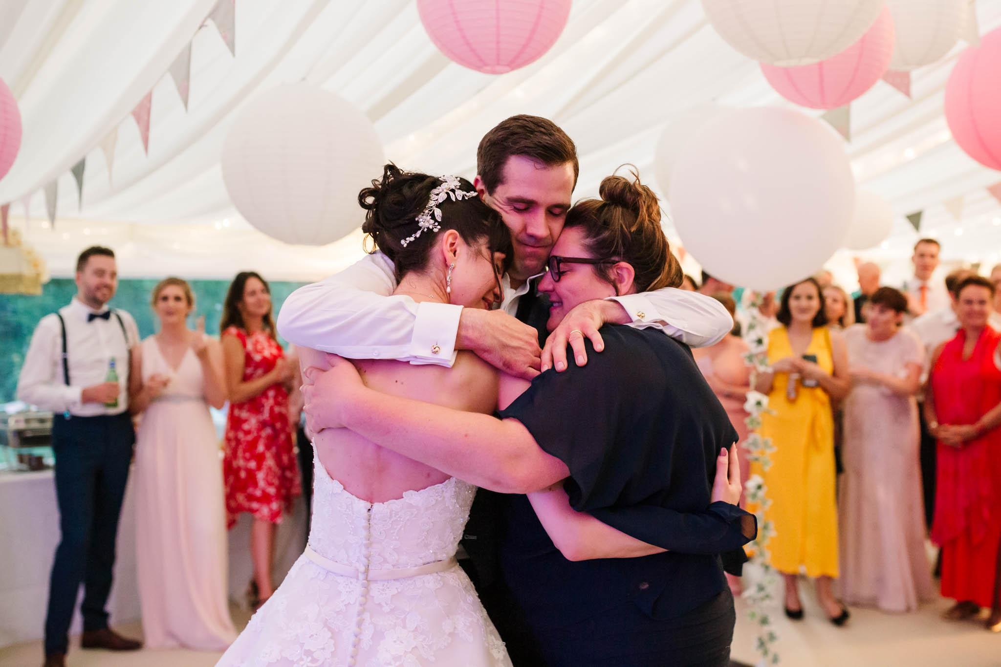 bride groom and sister hugging on dance floor