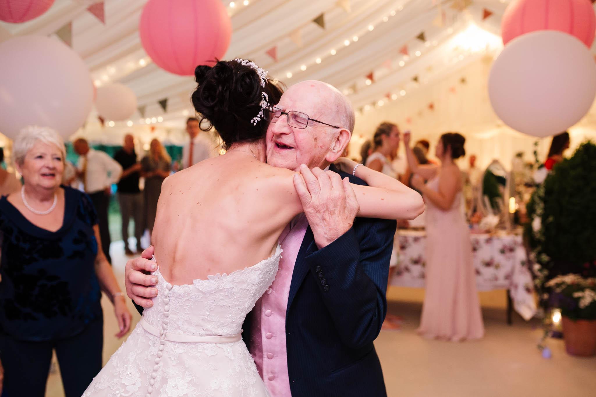 bride hugging grandad on dance floor