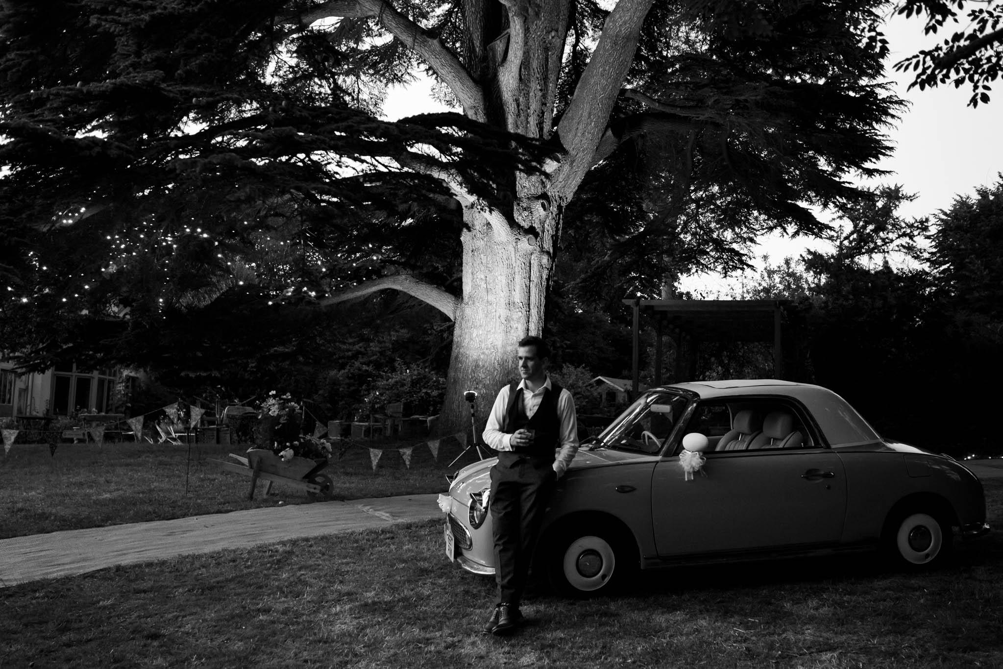 groom sitting on vintage car at night- alice in wonderland wedding