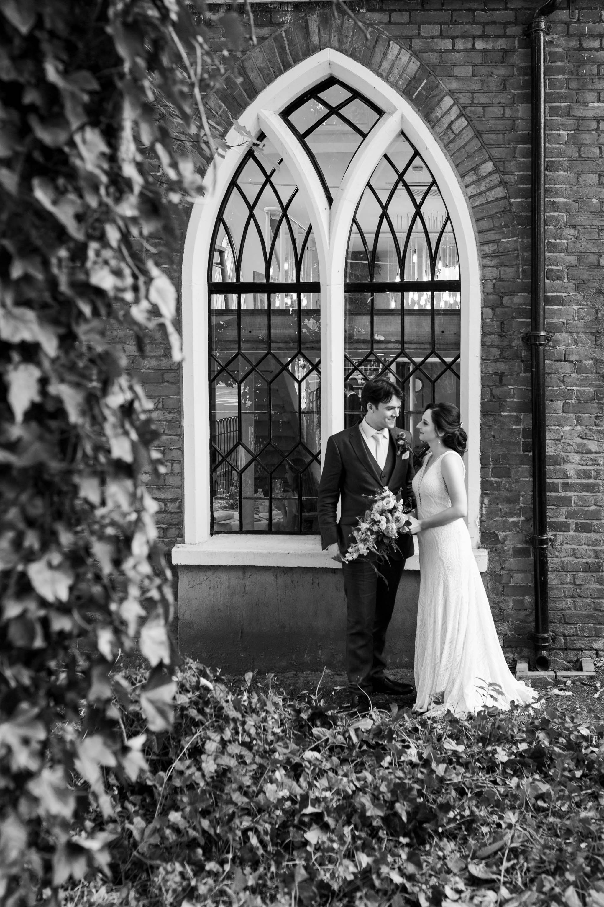 bride and groom outside church style window