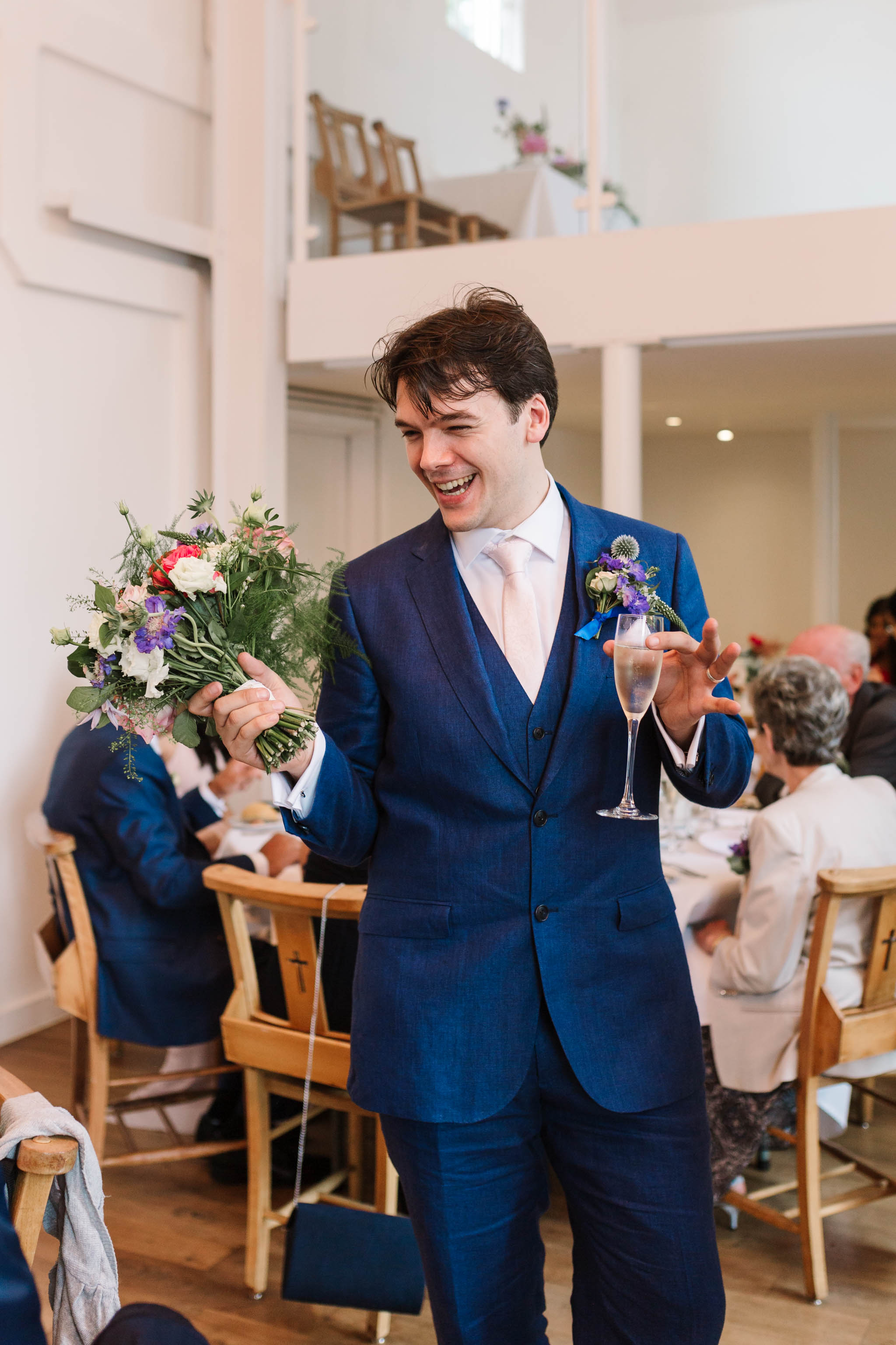 groom holding wedding bouquet and champagne