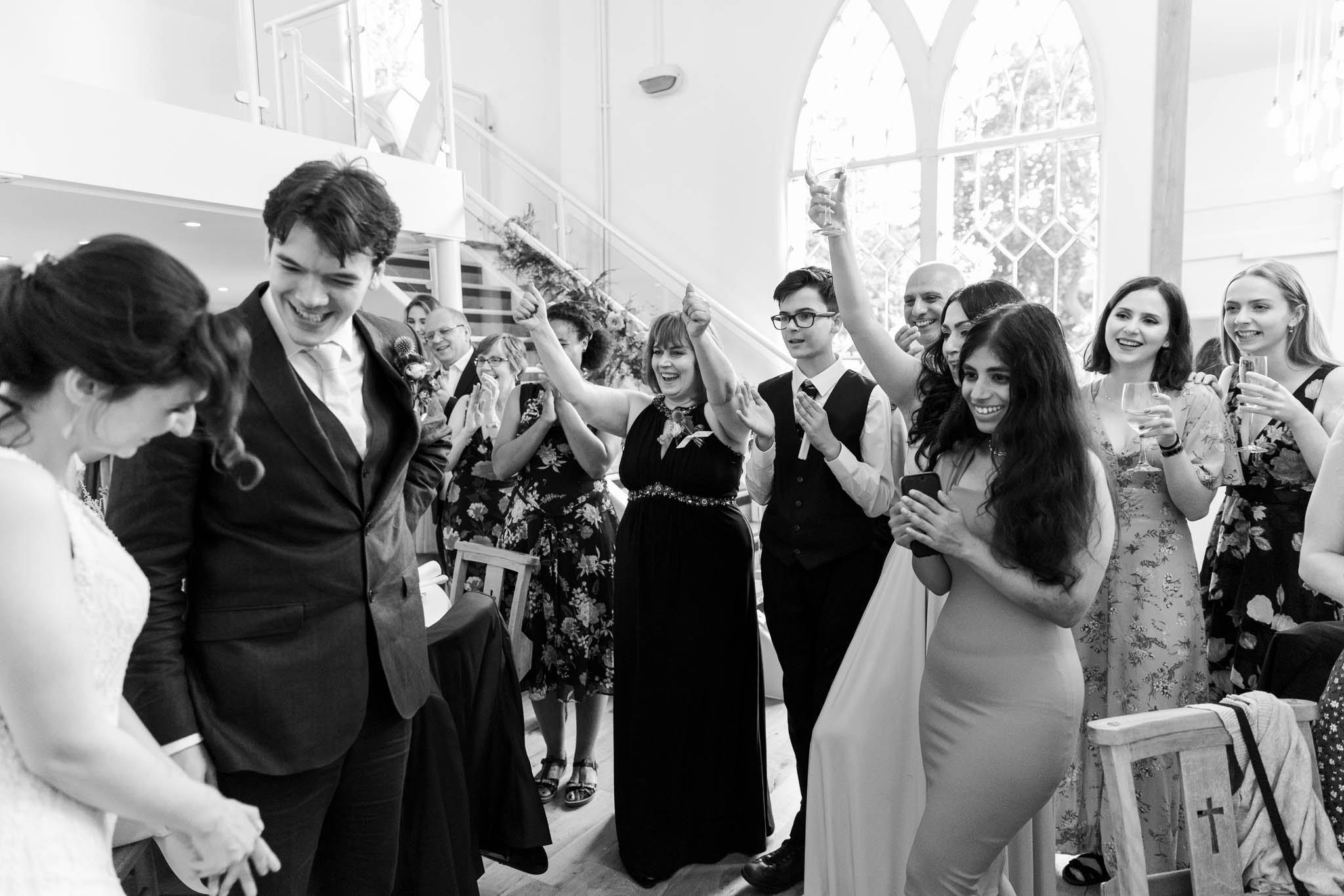 couple smiling and guests cheering at wedding