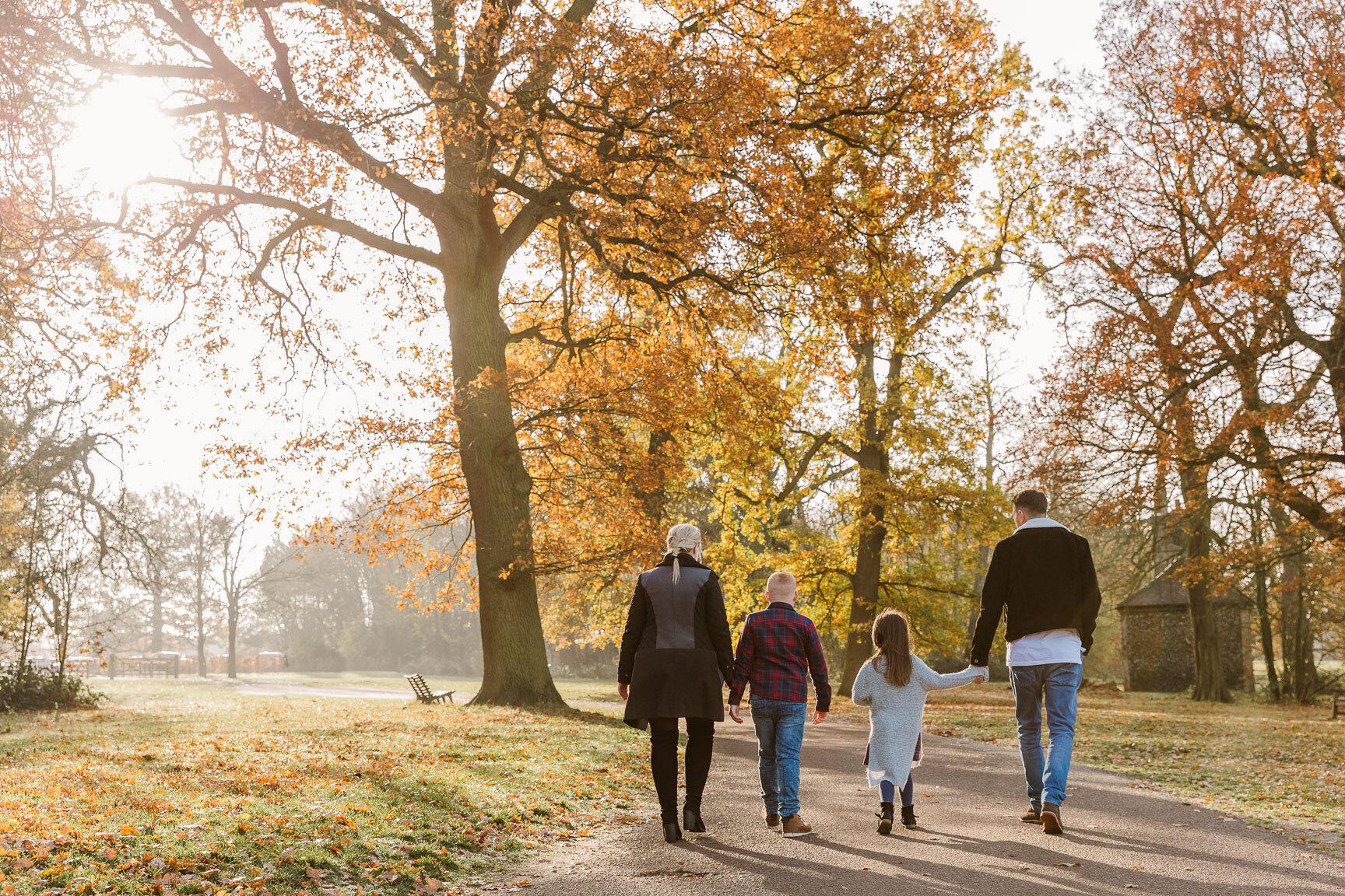 family walking through park in autumn