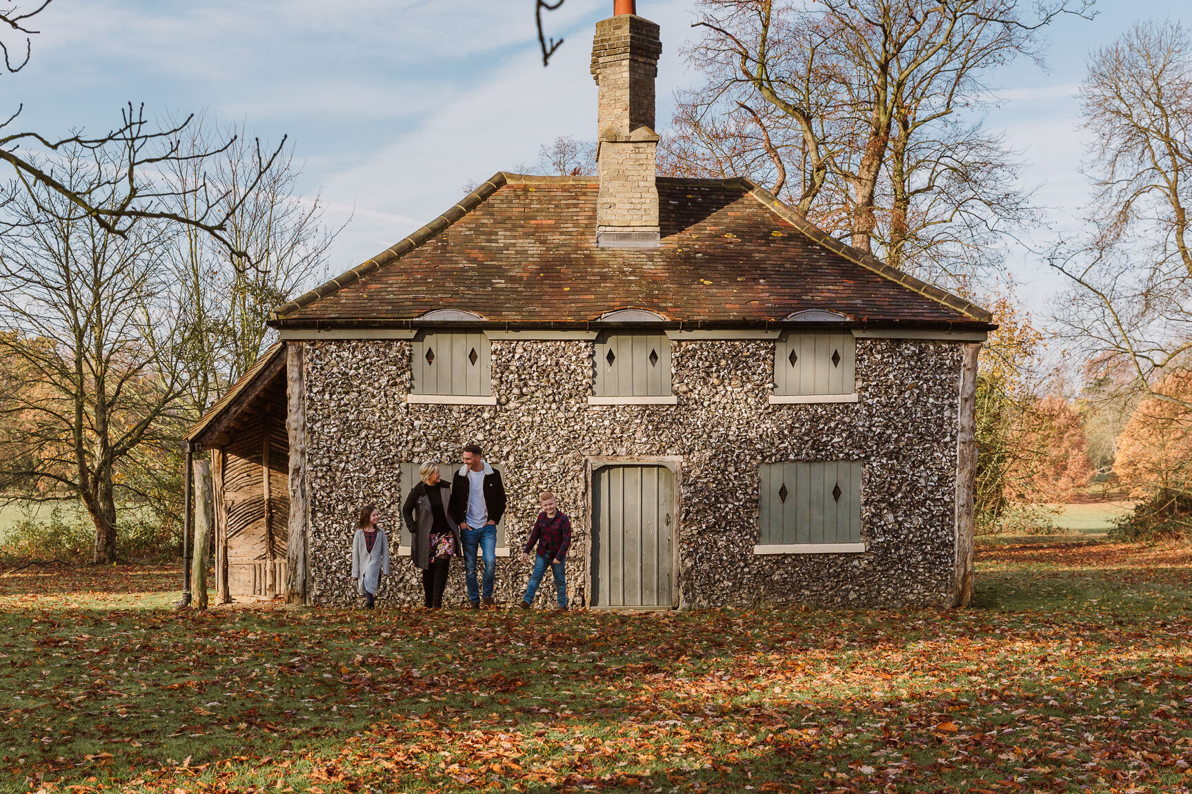 family in front of stone house in autumn