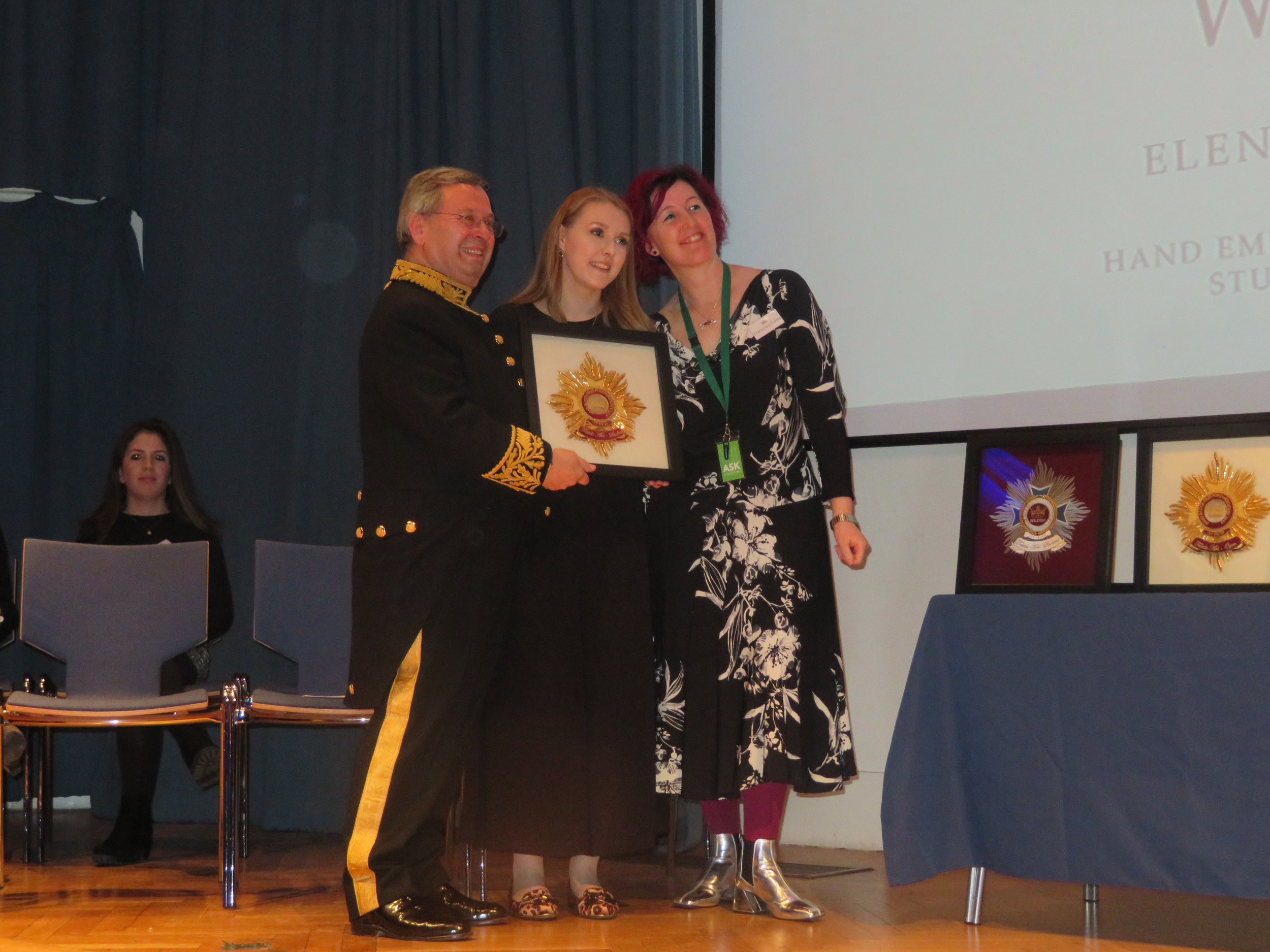 Chairman Alastair Macleod presenting Elena with Gold Award Student Textile with Representative of Brishopsgate Institute