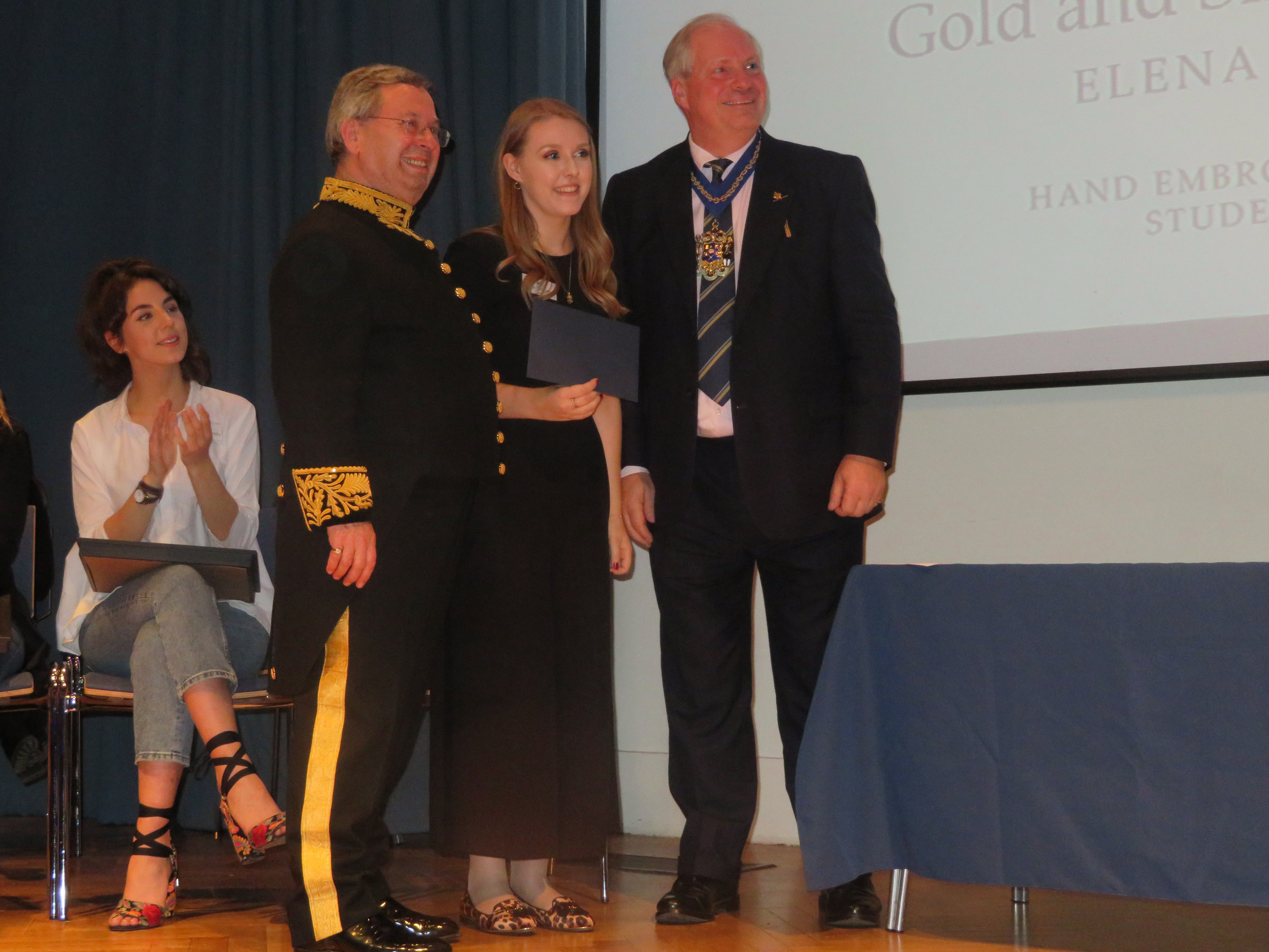 Chairman Alastair  Macleod, Elena Receiving the GSWD Goldwork Award from the Master Paul Constantinidi