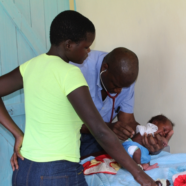 Dr. Moka Lantum treats a child with Meningitis while the boy's Mother watches. This became a turning point in Lantum's focus for Microclinic technologies.