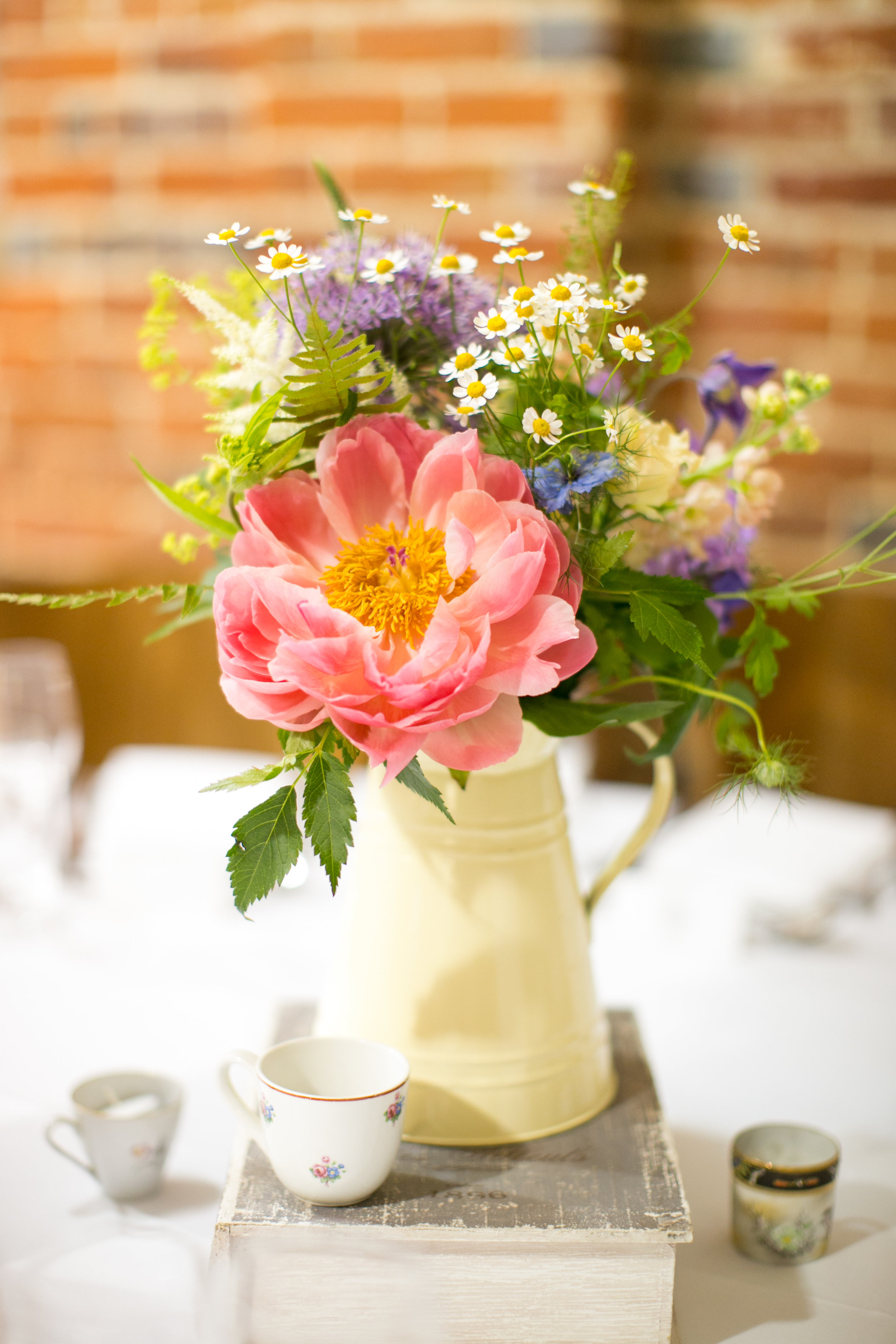 """It is not uncommon for me to make a miscellany of different arrangements for reception table centres. Using different vessels, I often elevate short vases and jugs by standing them on old books. I have a collection of little coffee cans which I use as tealight votives as shown here for this very simple relaxed styled wedding reception. I rarely make any table centre """"exactly"""" identical, I don't always have set lists of ingredients listing three of those and six of that but rather gather a selection of different elements for each table piece. For me, the varieties and and the colours will all come together on the day - it keeps the arrangements as you create them constantly fresh and exciting - (even when there are twenty or more to make)!"""