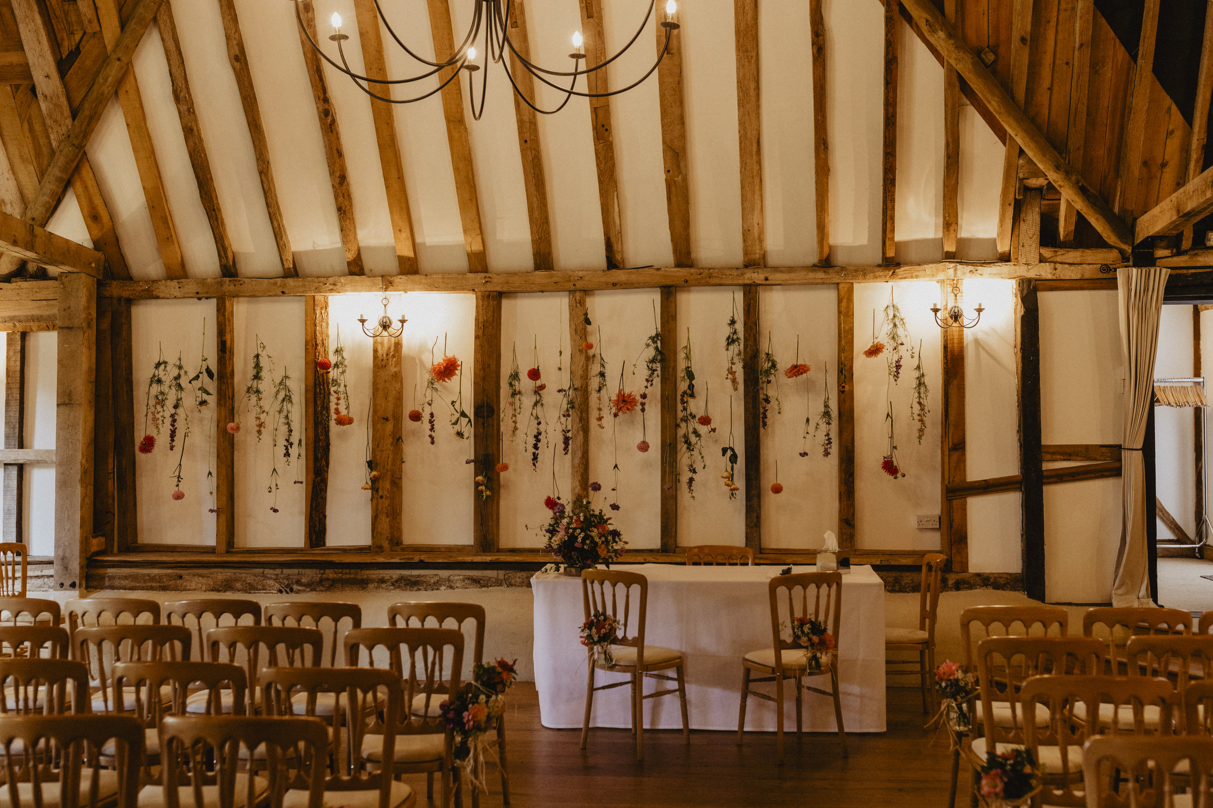 This is Clock Barn. I have strung flowers along the back wall which makes for a pretty back drop if you decide to have a ceremony here, it also provides a pretty backdrop for the drinks reception and looks mighty fine when the disco begins!