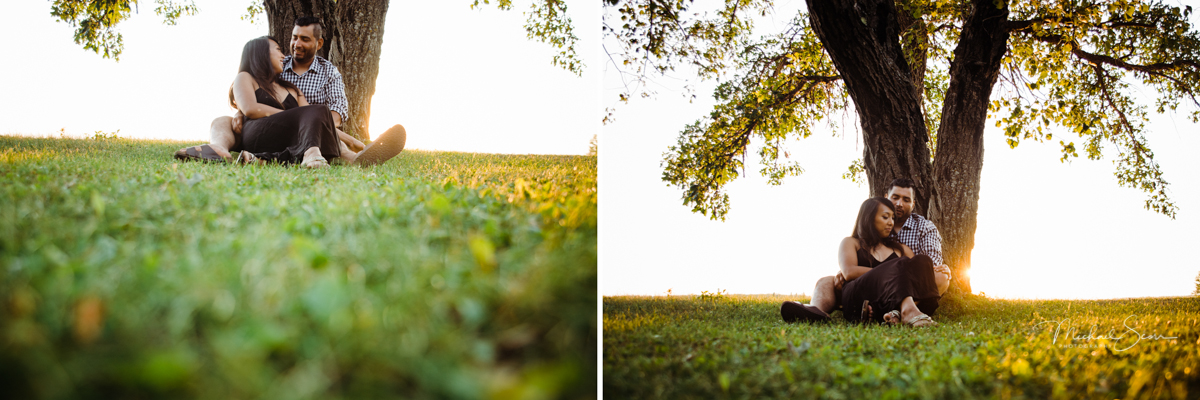 Winnipeg couple sat down beside a tree with sun setting in the background
