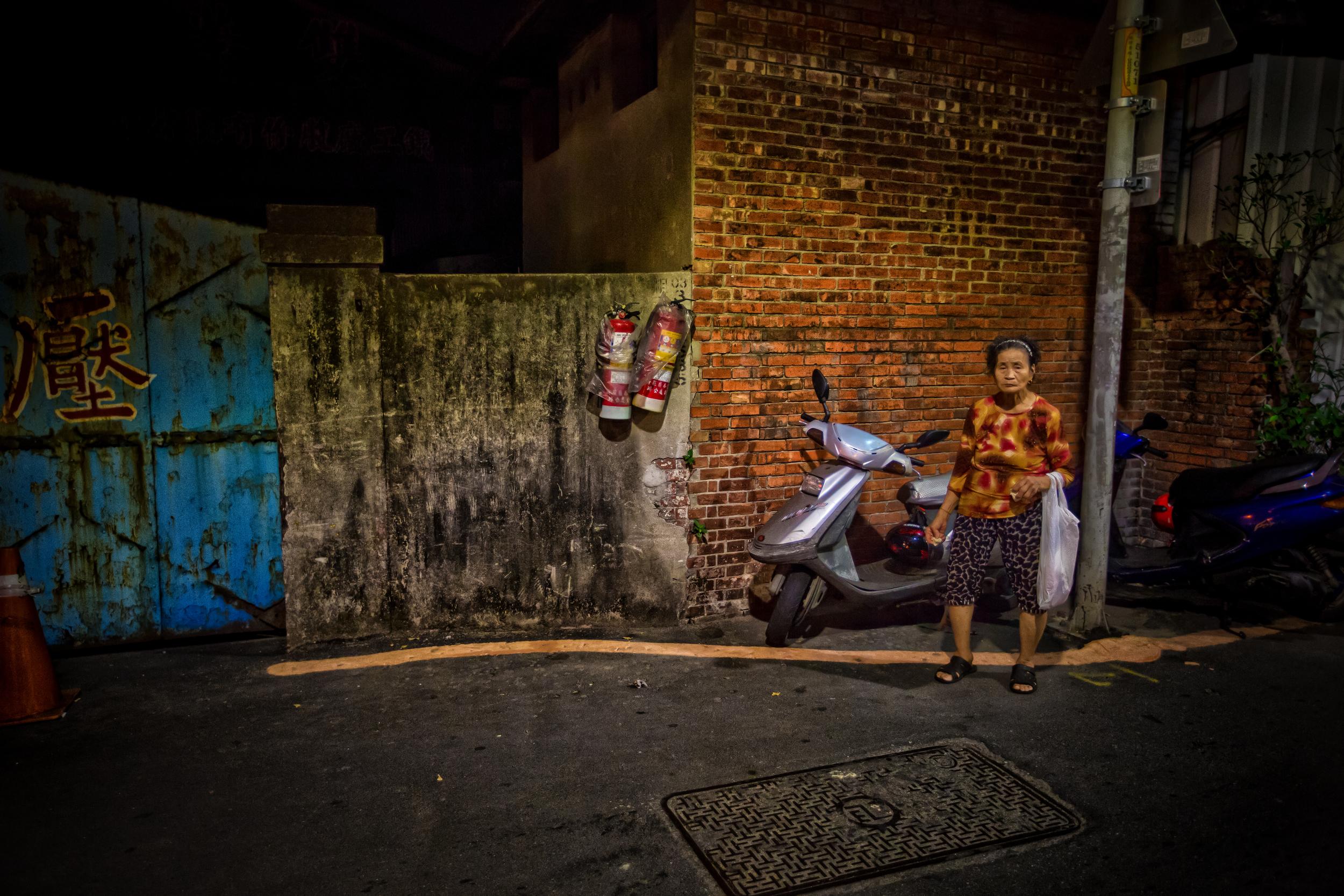 An elderly Taiwanese women in a back alley near Temple Street