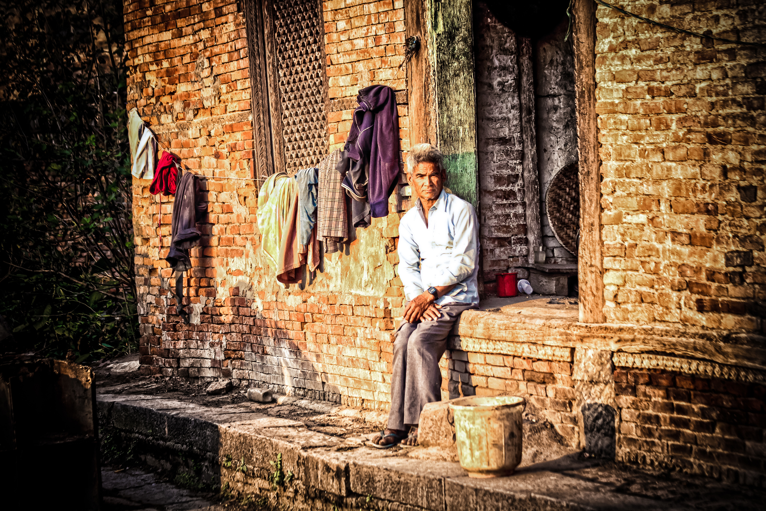 - A Nepali man outside of his house in Kathmandu with his drying clothing.