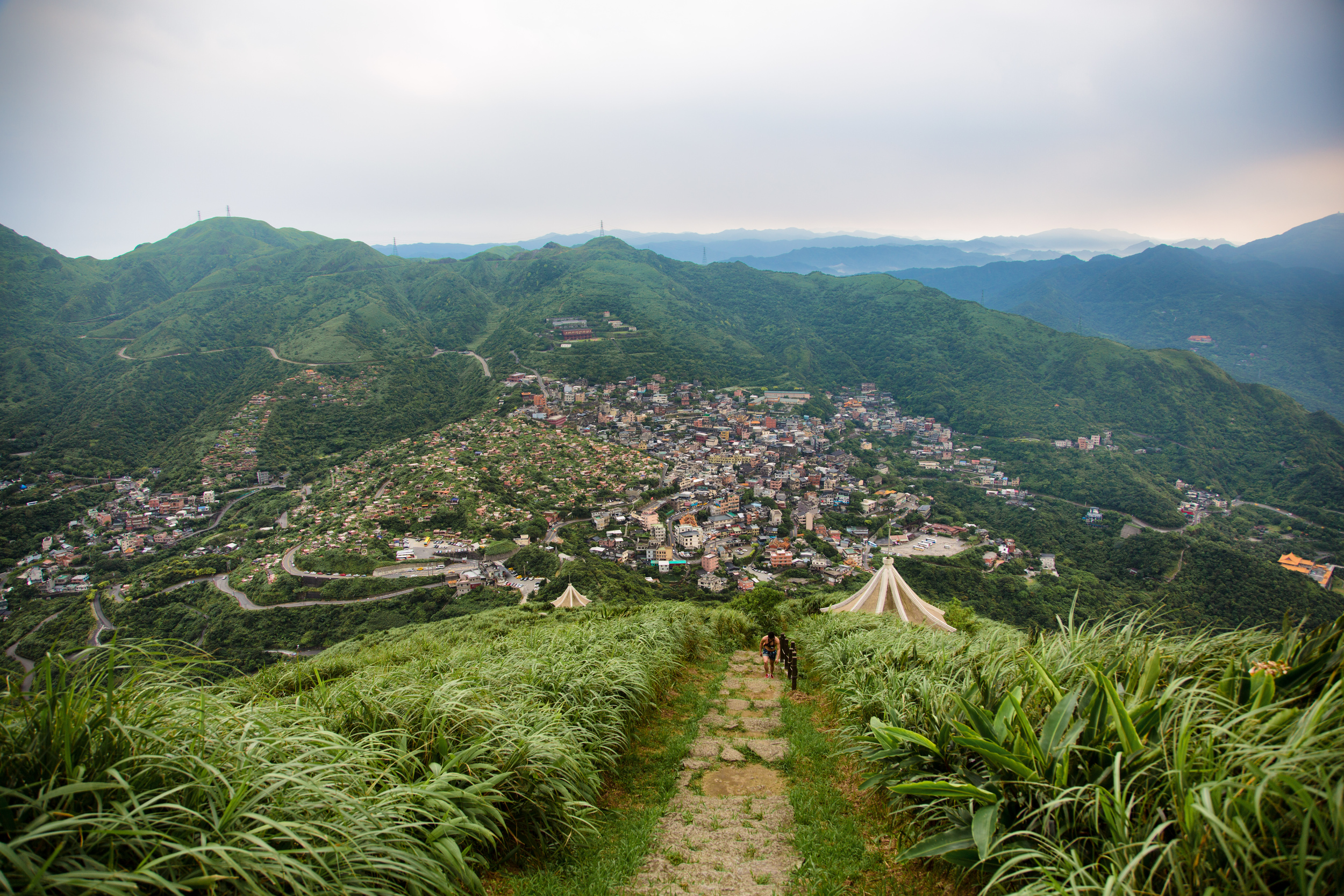 A hiker on his way to the peak of Jilong Mountain (雞籠山) with Jiufen in the background