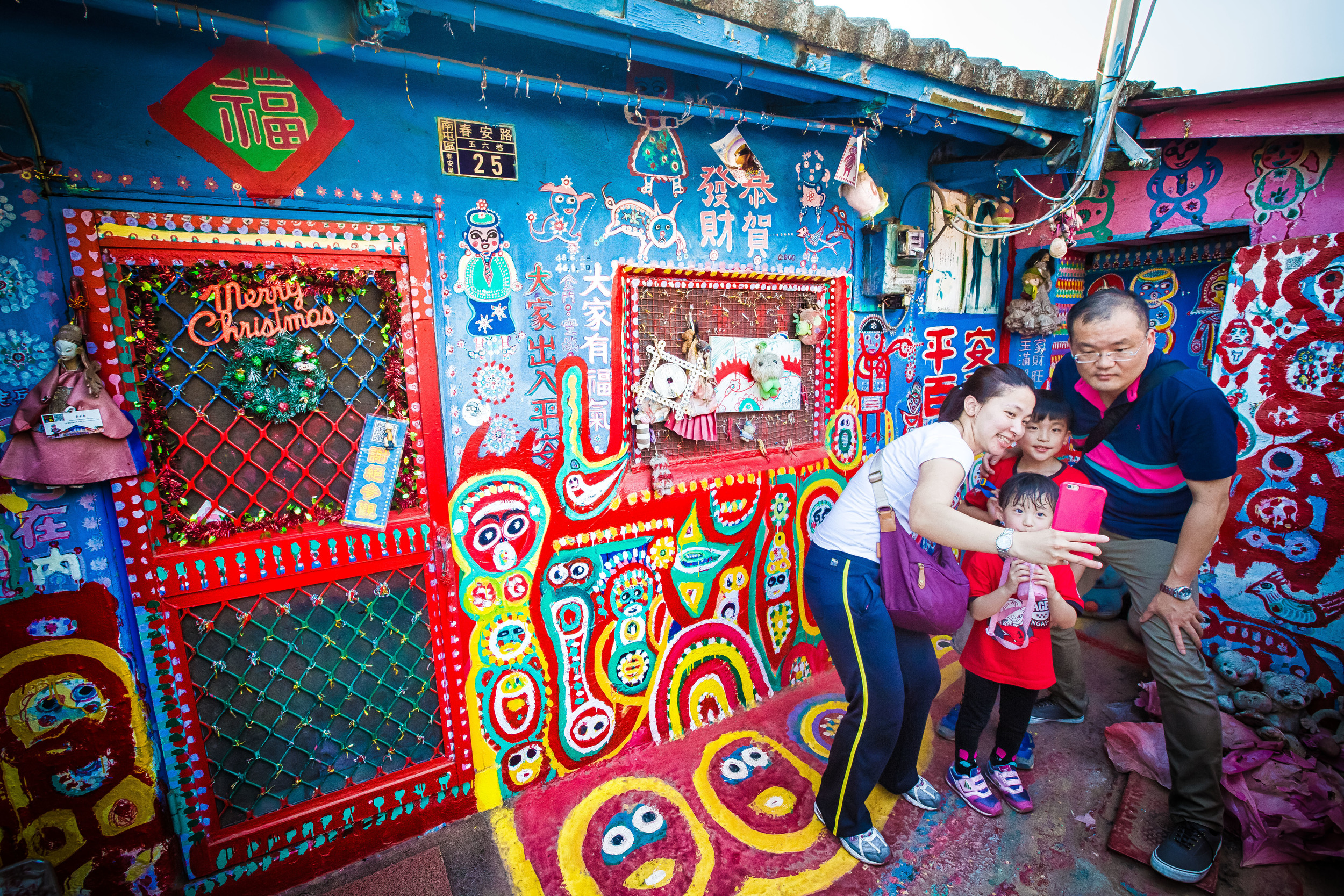 A family taking some selfies at the Rainbow Village.